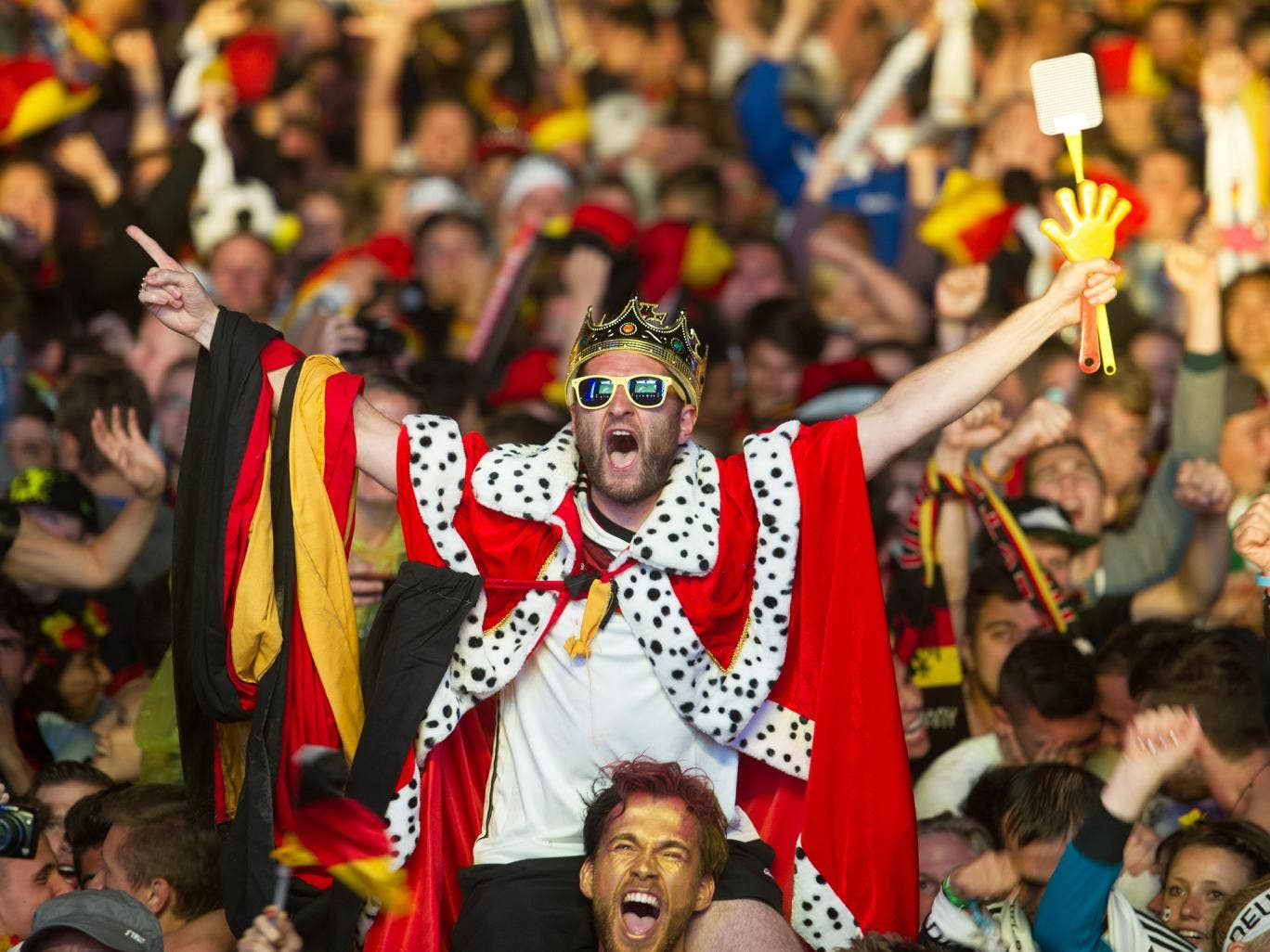 German soccer fans react after the deciding goal  for Germany in the final of  the Brazil World Cup 2014 between Germany and Argentina played in Rio de Janeiro, Brazil, at a public viewing  area  called 'Fan Mile' in Berlin