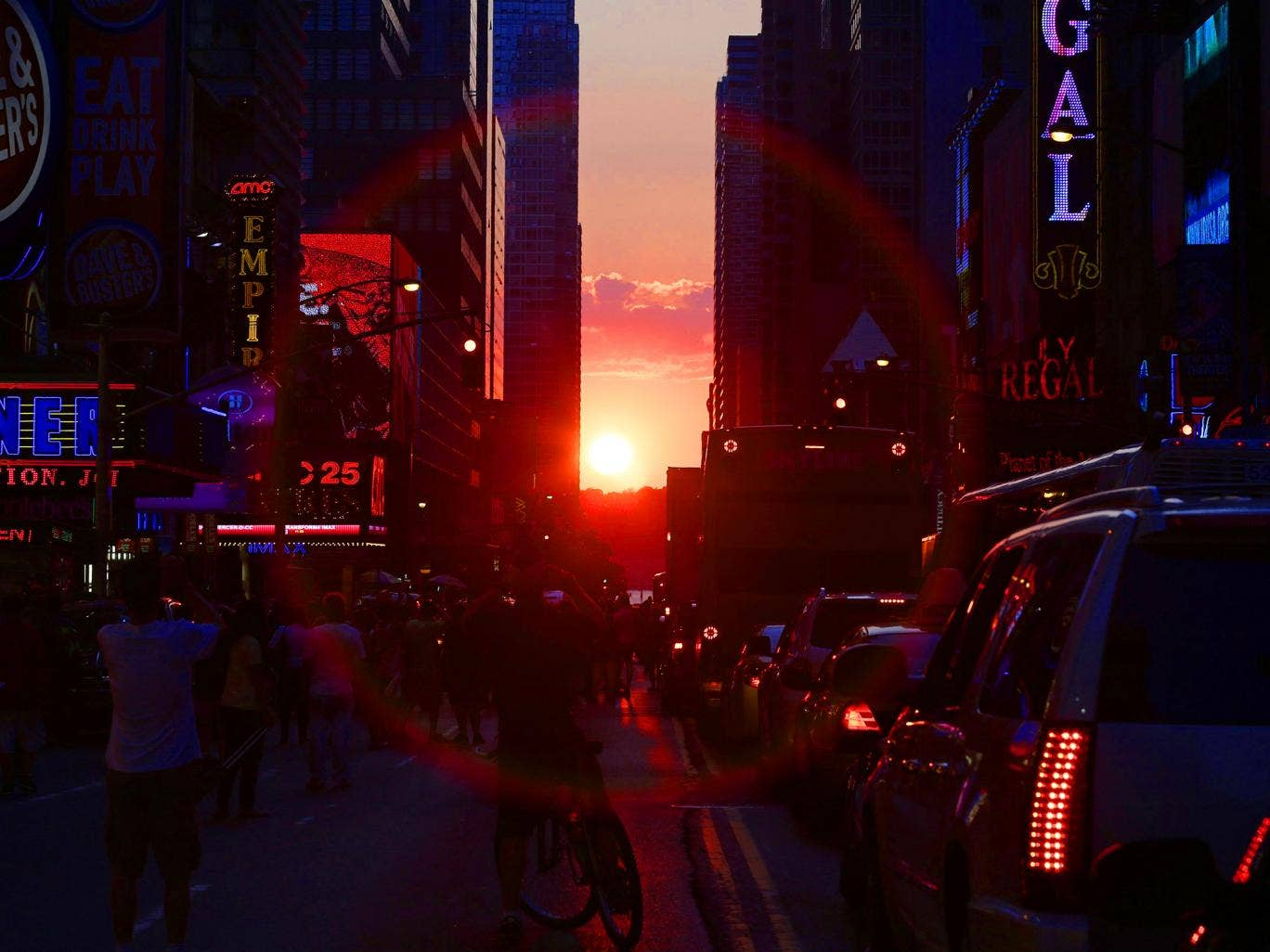 The sun is seen setting behind buildings in Times Square during the Manhattanhenge