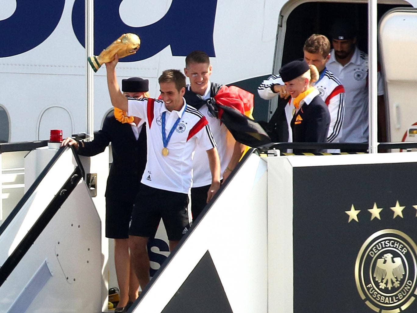Philipp Lahm alights the plane with the World Cup