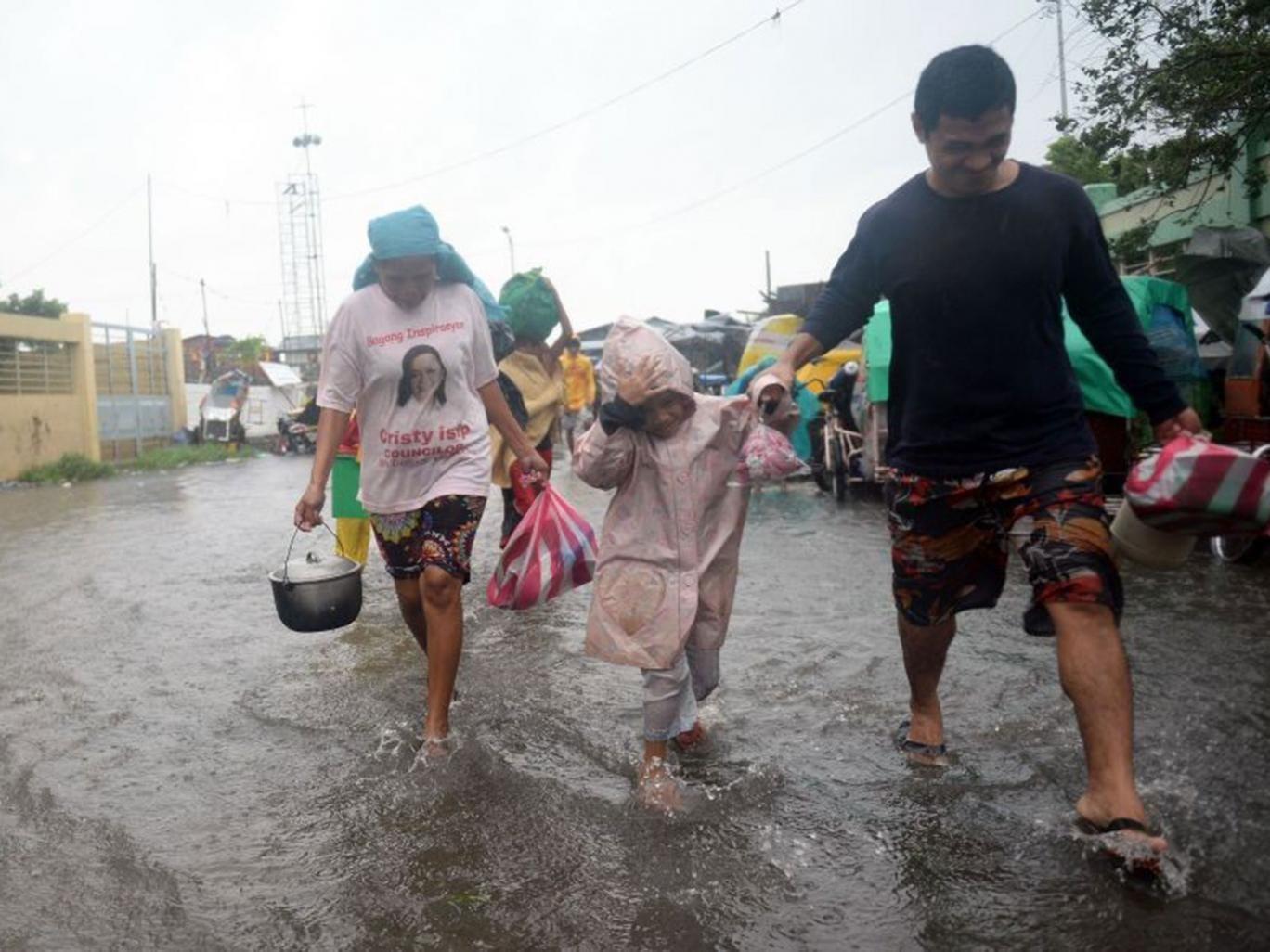 Residents cross a flooded street to an evacuation center as Typhoon Rammasun/Glenda barrels across Manila
