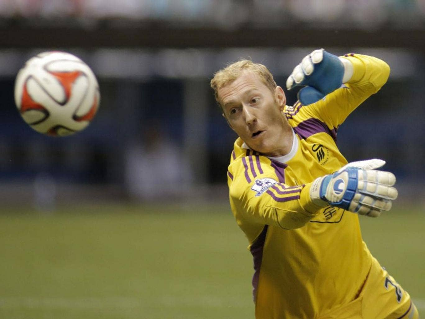 Swansea City goalie  Gerhard Tremmel  attempts to block a shot on goal from Chivas De Guadalajara during the second half of a International League soccer match at Miller Park Wednesday, July 16, 2014, in Milwaukee.