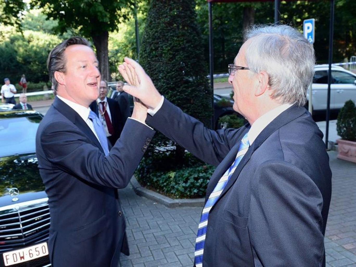Jean-Claude Juncker high-fives David Cameron at the European Parliament in Brussels, Belgium.