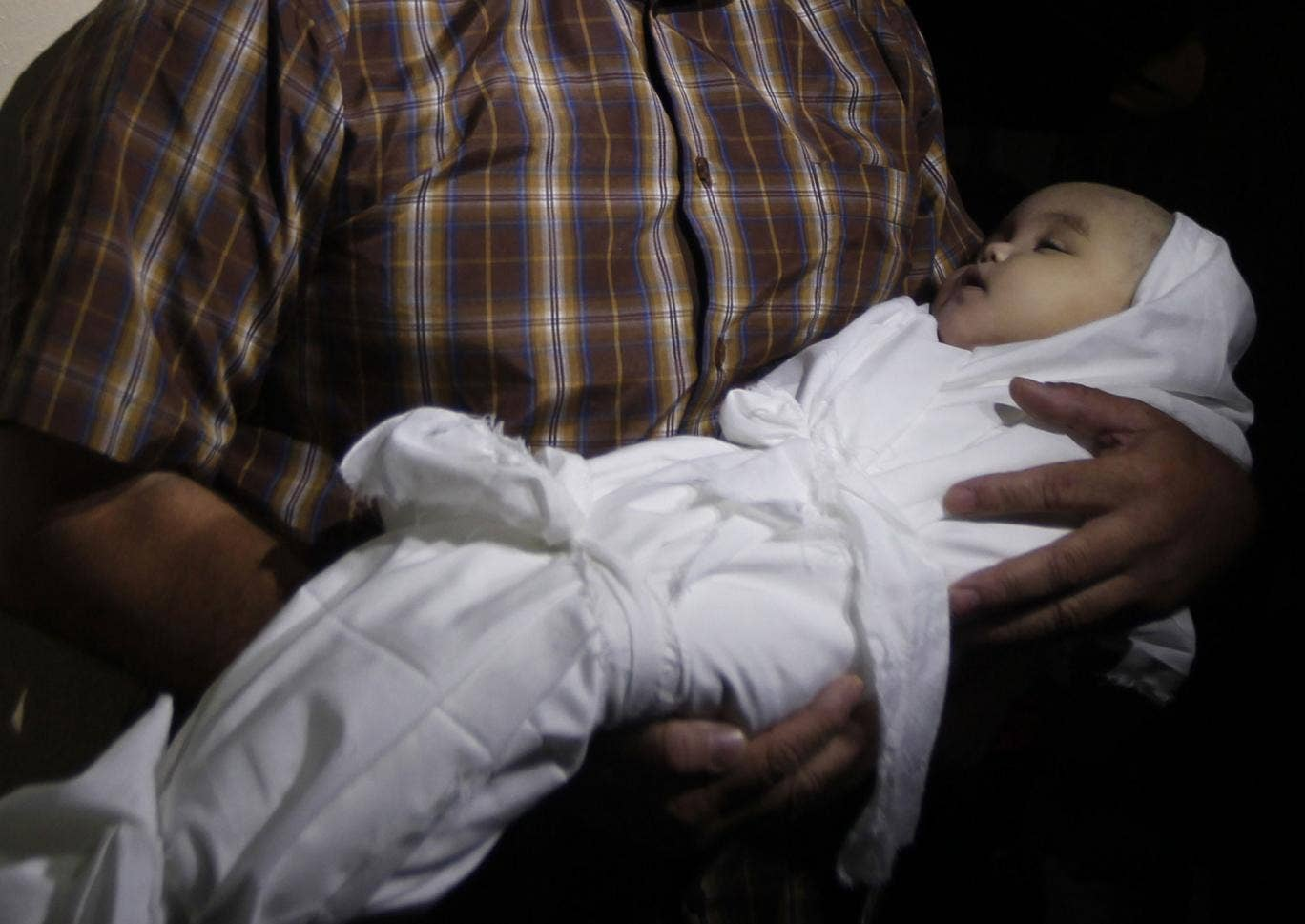 A Palestinian mourner carries the body of five-month-old girl Lama al-Satri after she was killed in an Israeli air strike the previous day, during her funeral in Rafah in the southern Gaza Strip