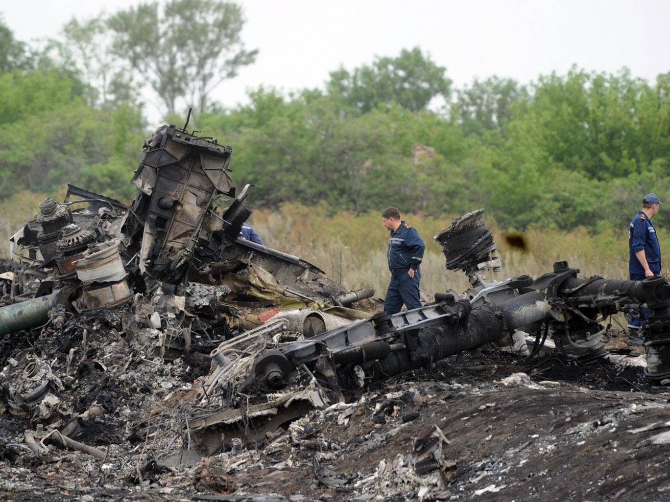 Rescuers stand on the site of the crash of a Malaysian airliner near the town of Shaktarsk, in rebel-held east Ukraine