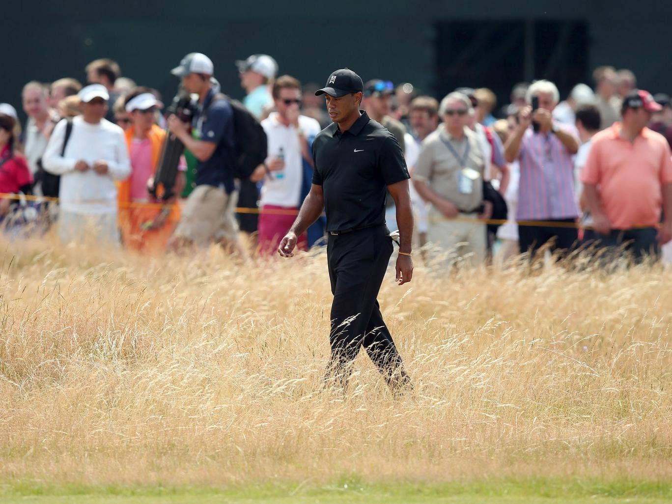 Tiger Woods goes searching for his ball in the rough after a stray drive on the first hole of the day
