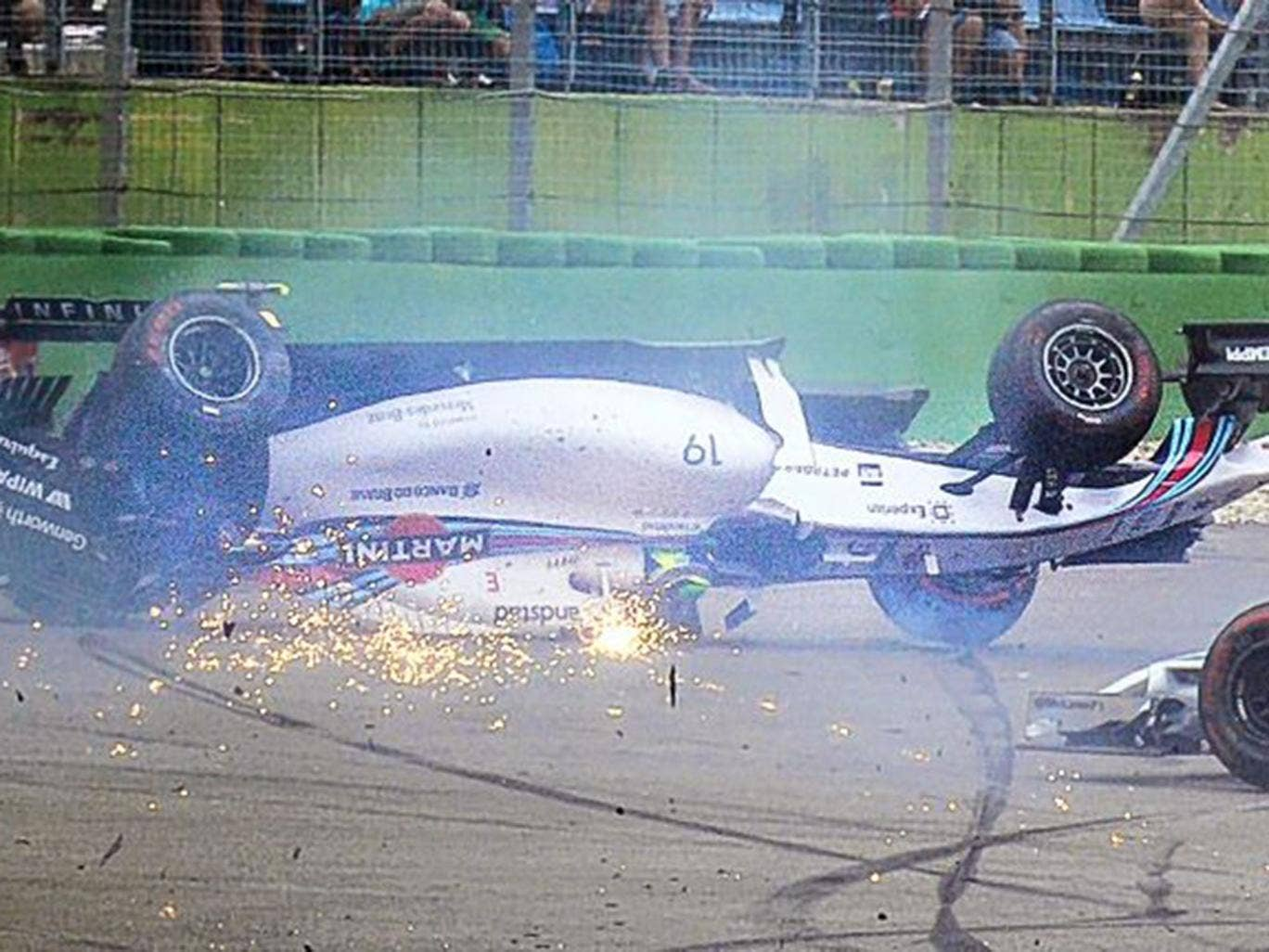 Felipe Massa's Williams ends upside down after colliding with Kevin Magnussen's McLaren at the first corner