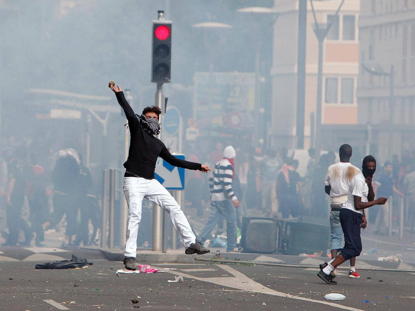A rioter throws a stone towards riot police following a pro-Palestinians demonstration, in Sarcelles, north of Paris