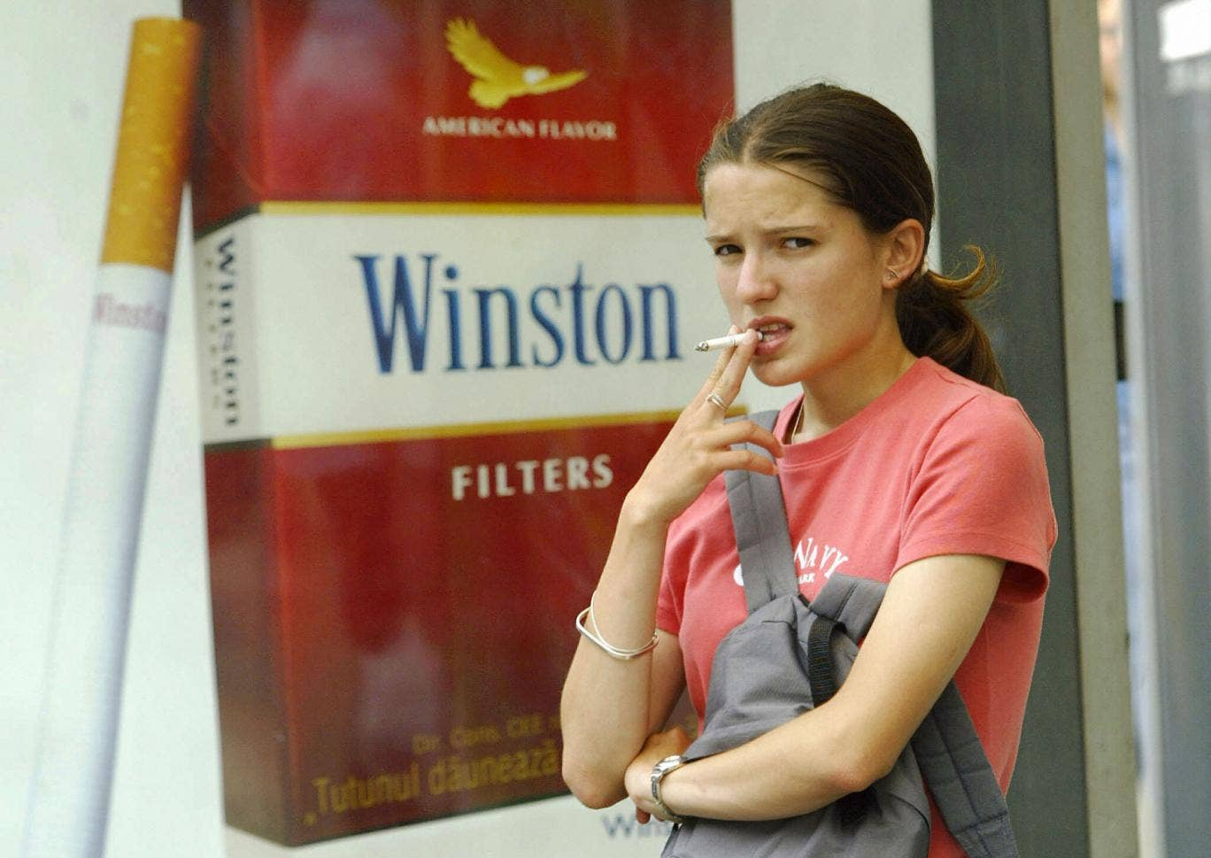 A young girl smokes near a commercial for cigarettes
