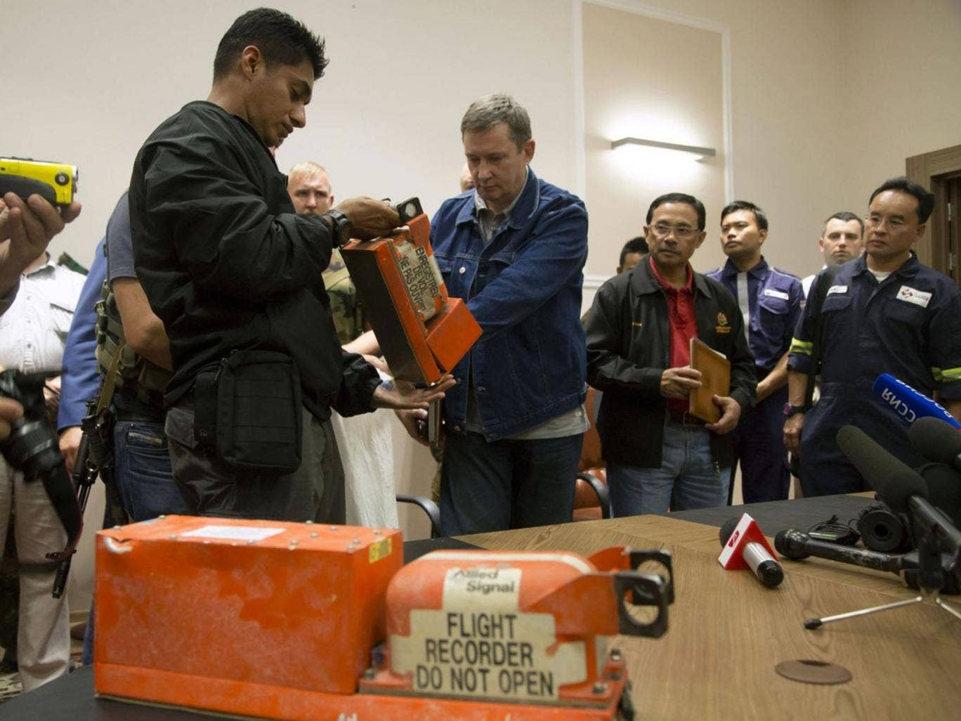 A Donetsk People's Republic official, right, hands over a flight recorder to a Malaysian investigator
