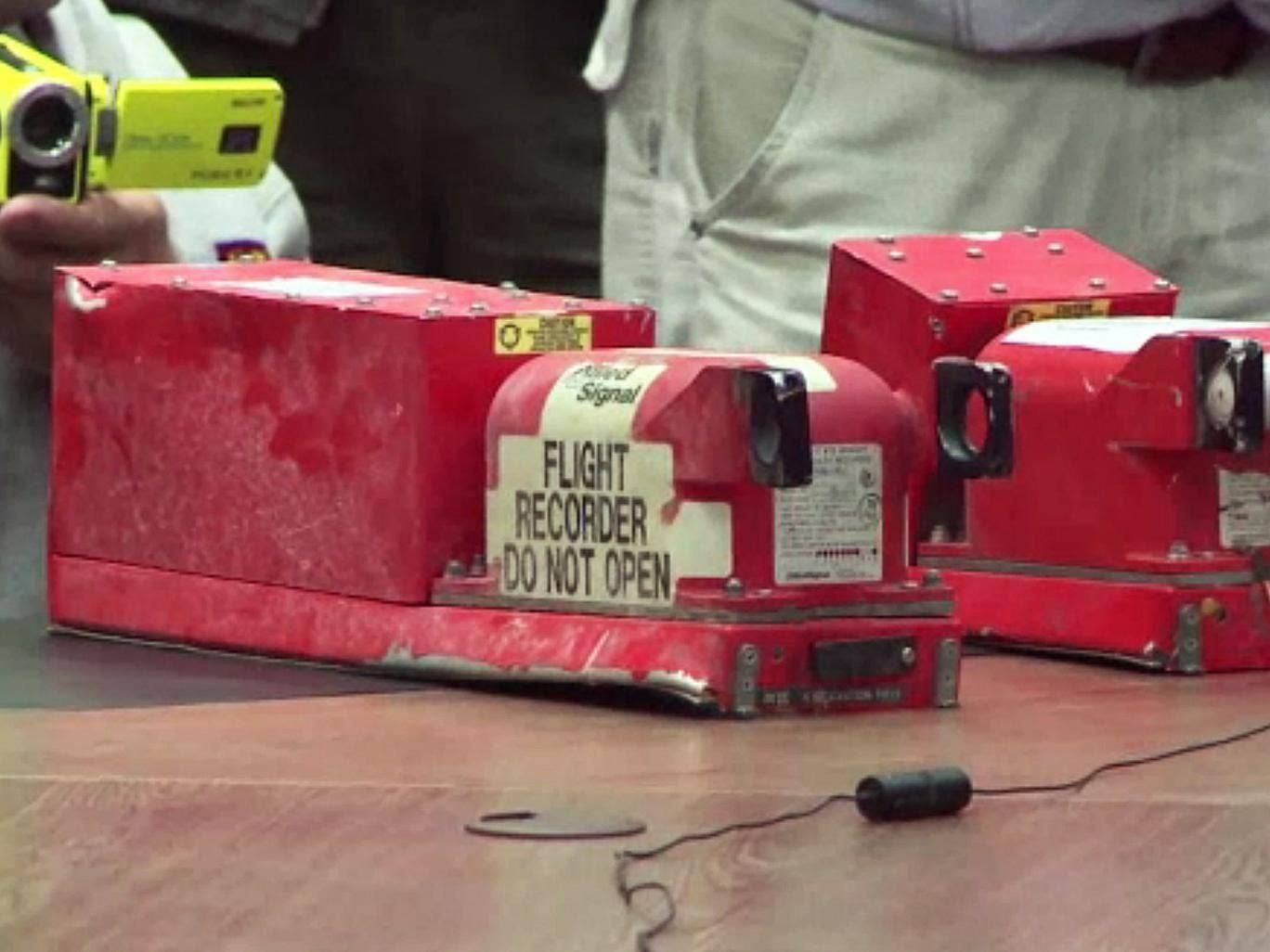 Two black boxes recovered from the crash site of the MH17 jet being handed over to Malaysian officials during a press conference in Donetsk