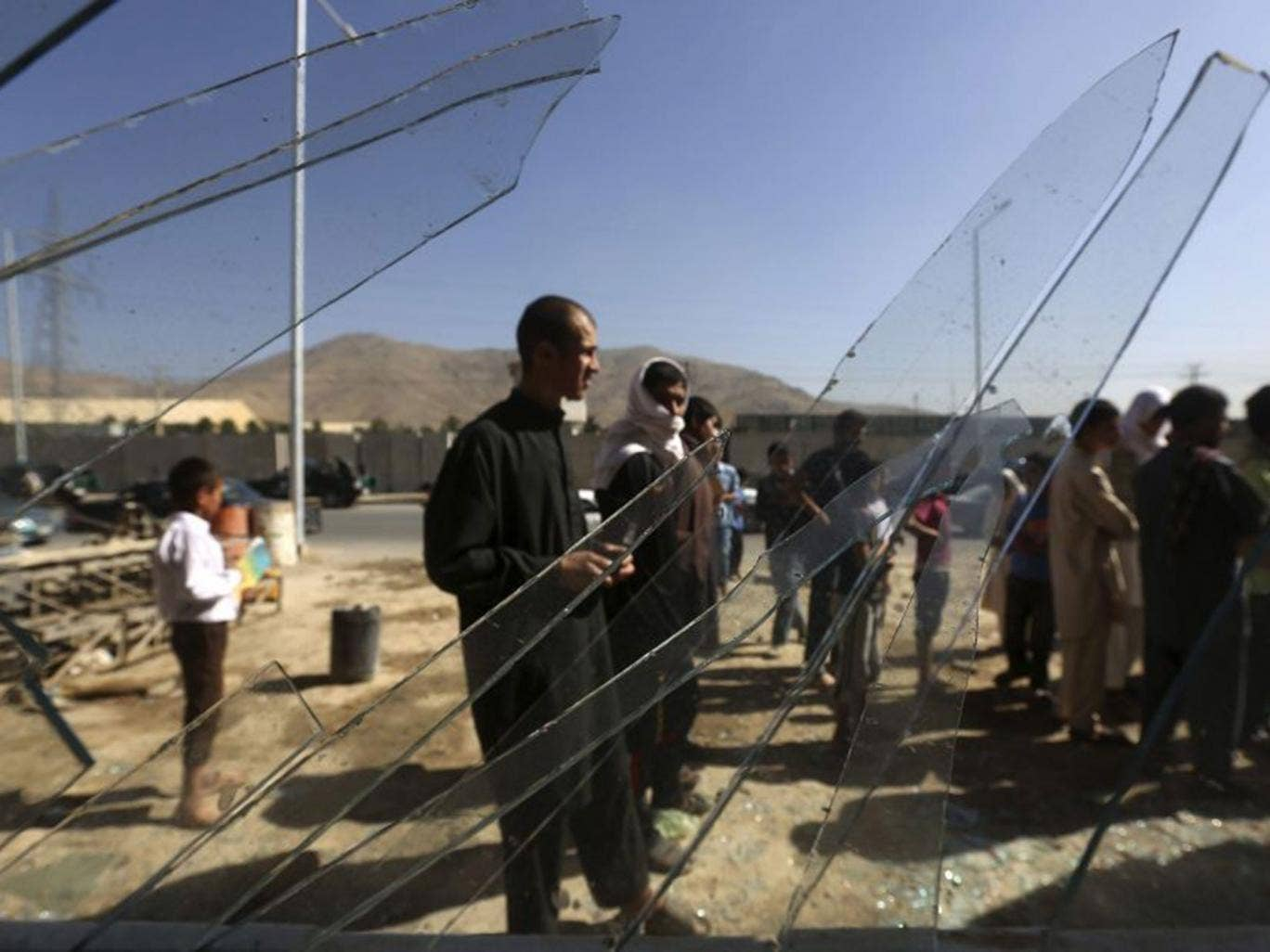 Afghans are seen through broken glass at a shop at the site of the blast