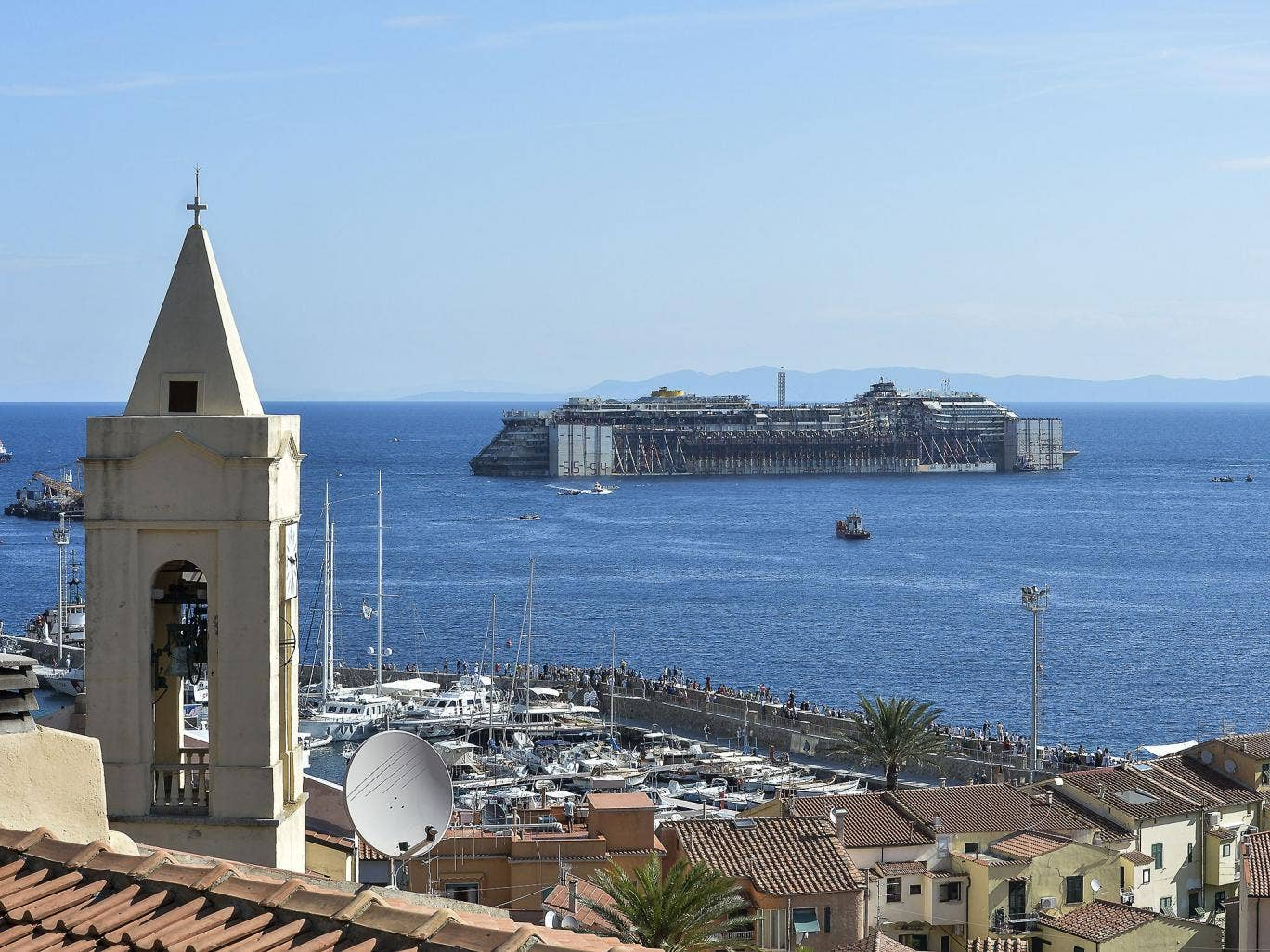 The wreck of the Costa Concordia is towed away from Giglio more than two-and-a-half-years after it sunk. In the foreground is the steeple of the church where many of the survivors were brought for refuge on 13 January 2012