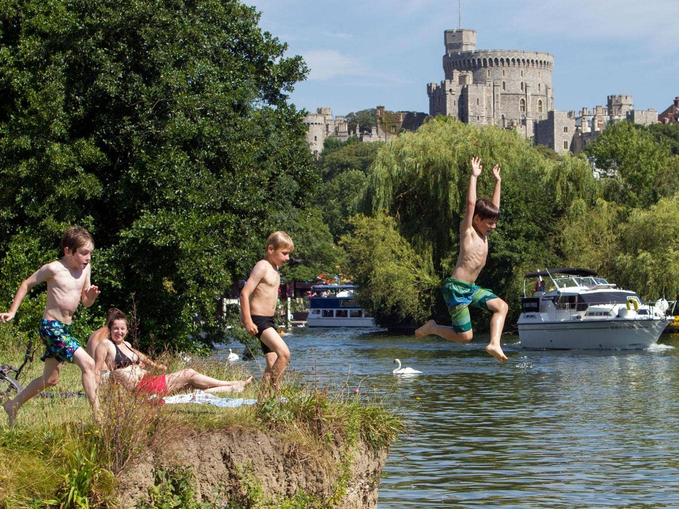 Elliott Duko (R) with Charles Keen (L) and Harry O'Shaughnesy (C) cool off by jumping into river Thames in Windsor