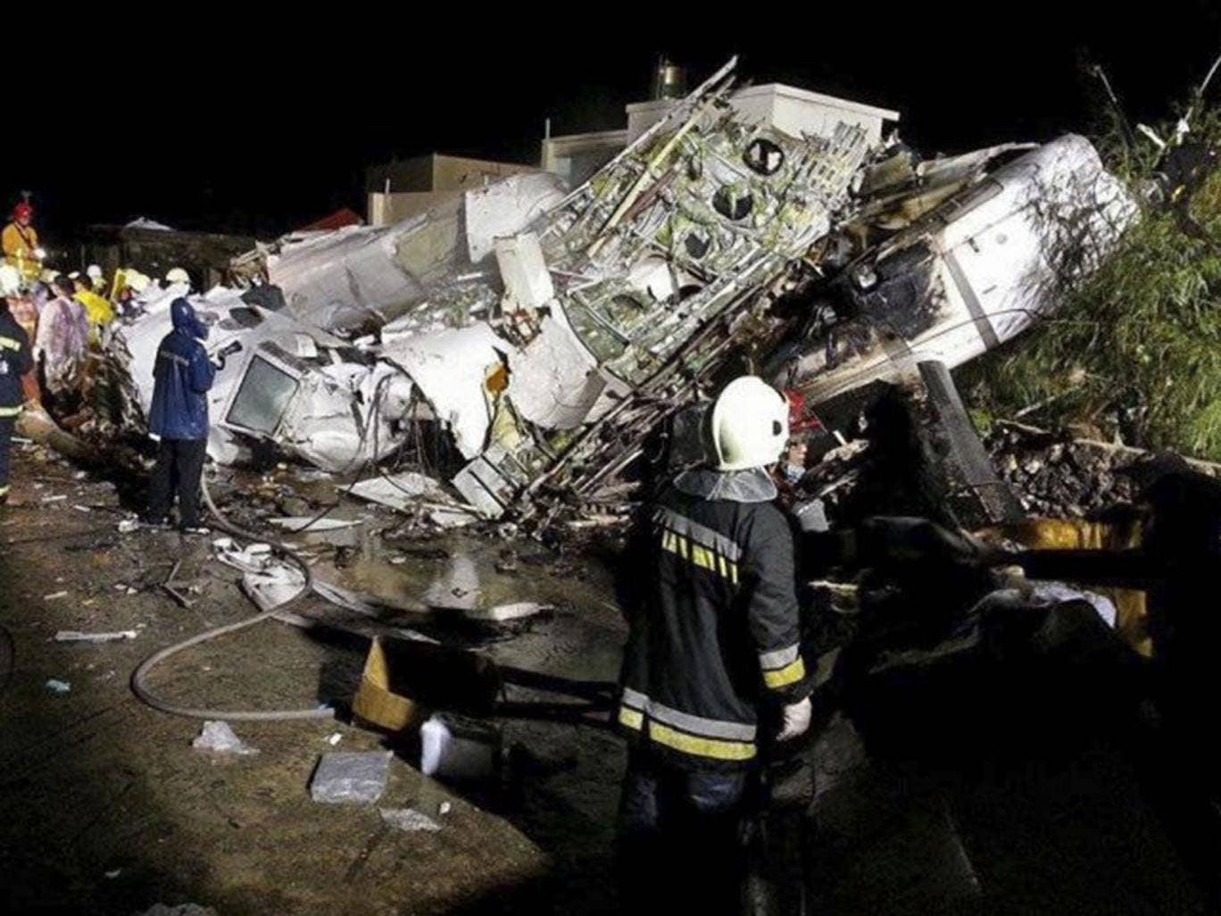 Rescue workers survey the wreckage of TransAsia Airways flight GE222 which crashed while attempting to land in stormy weather on the Taiwanese island of Penghu, late Wednesday, July 23, 2014. A transport minister said dozens of people were trapped and fea