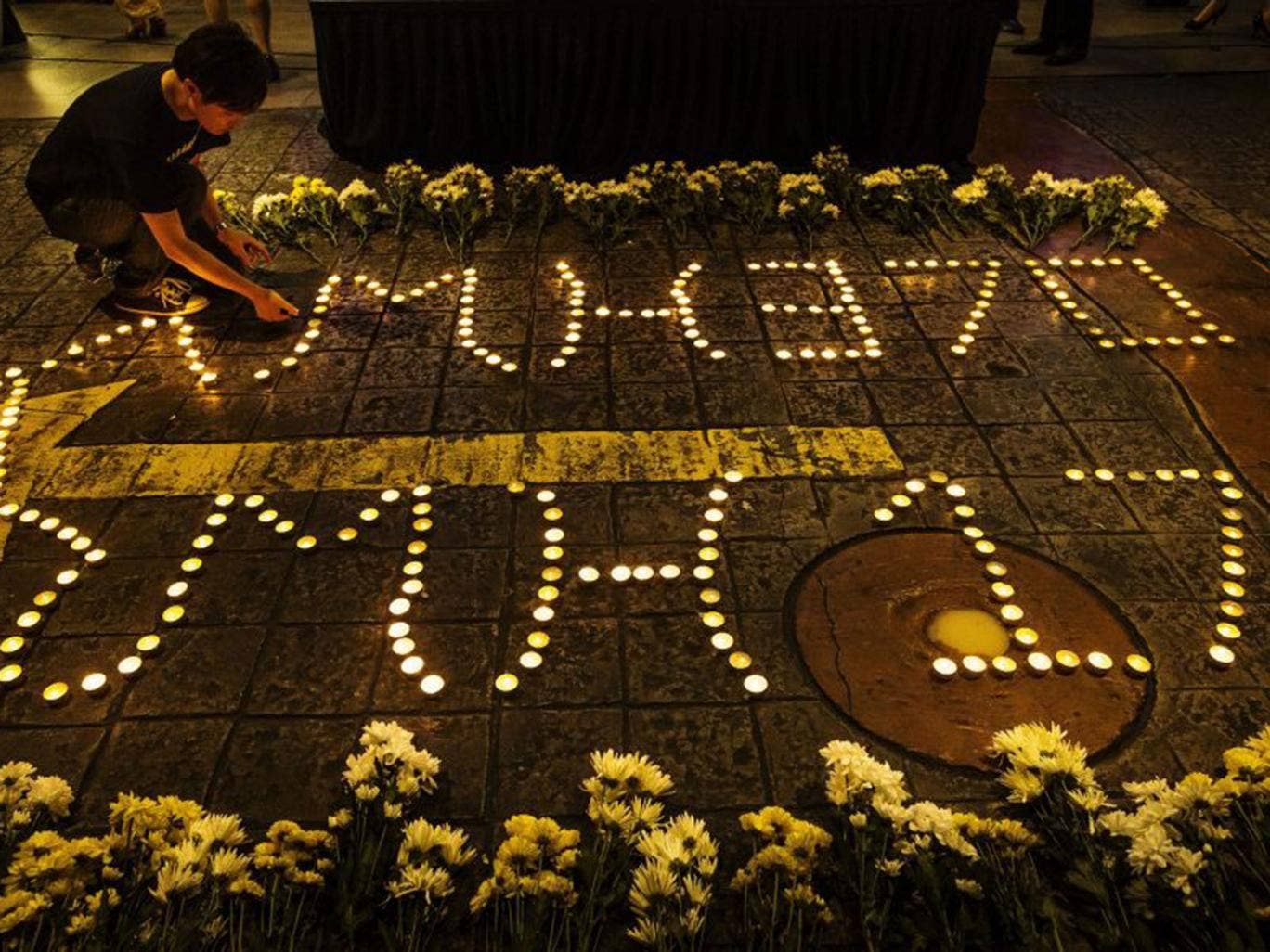 A Malaysian man lights up candles during a vigil in remembrance for passengers and crew of the Malaysian Airline flight MH370 & MH17 in Petaling Jaya near Kuala Lumpur, Malaysia