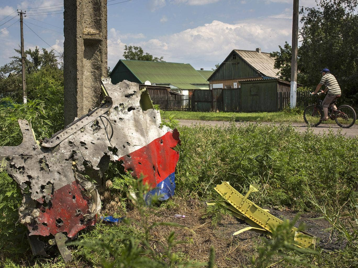 A man cycles past a piece of the wreckage of the Malaysia Airlines flight MH17 in Petropavlivka, Ukraine