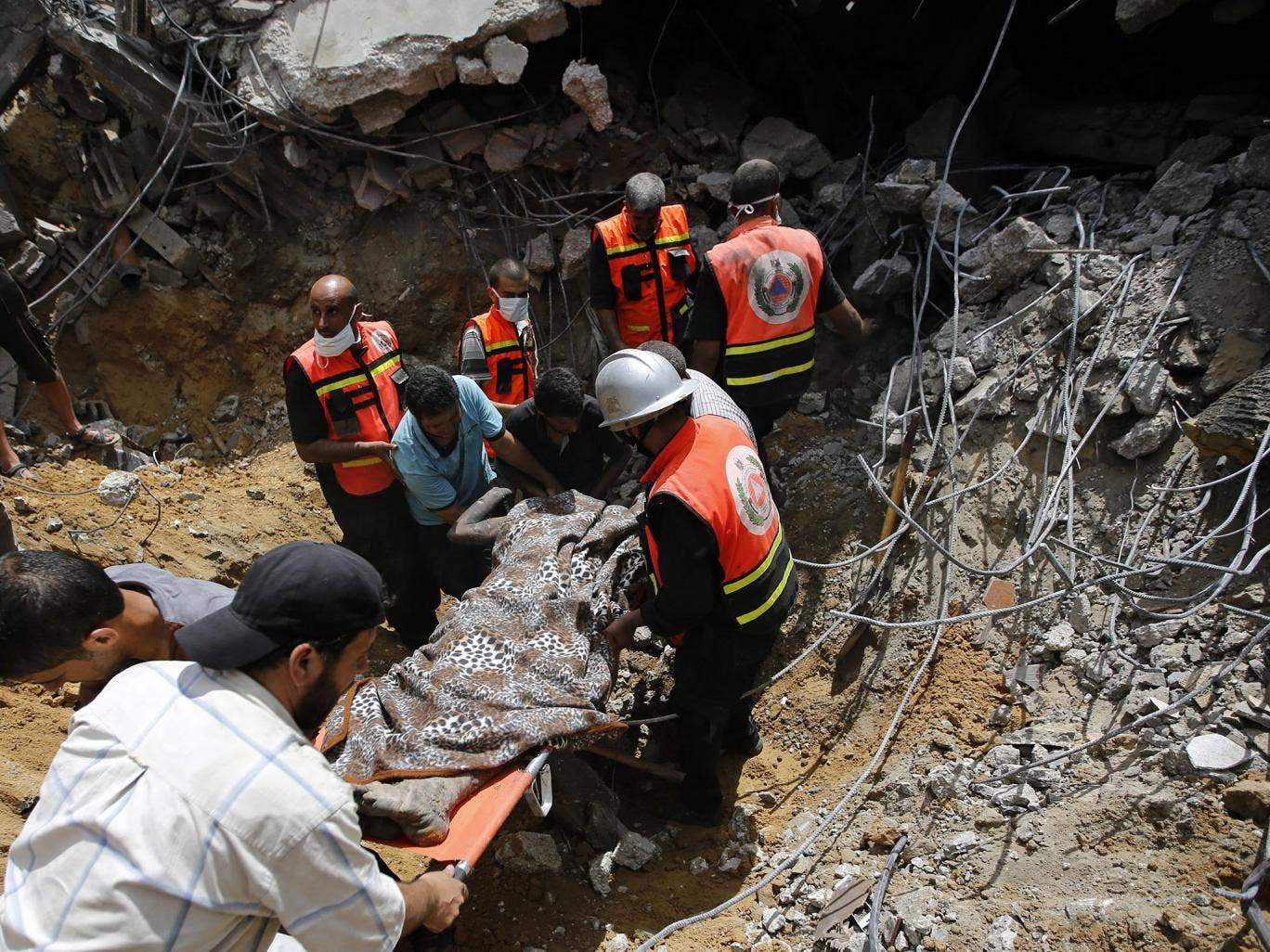 Medics recover a body from a destroyed house in Khan Younis