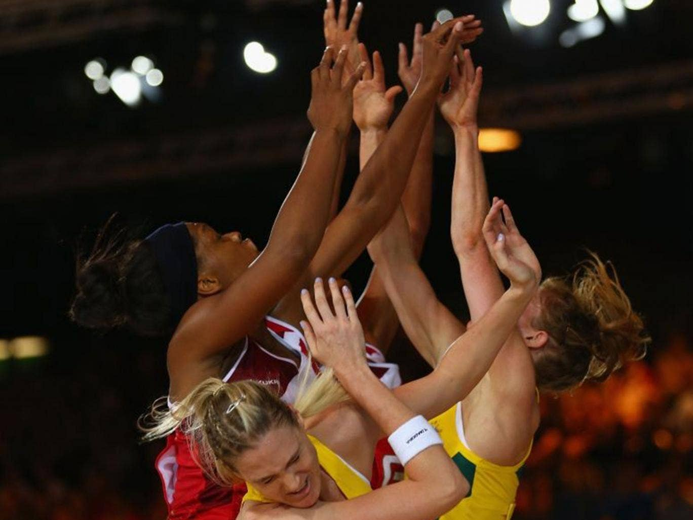 Gold rush: England (left) and Australia netball players challenge for the ball and potentially the ultimate prize
