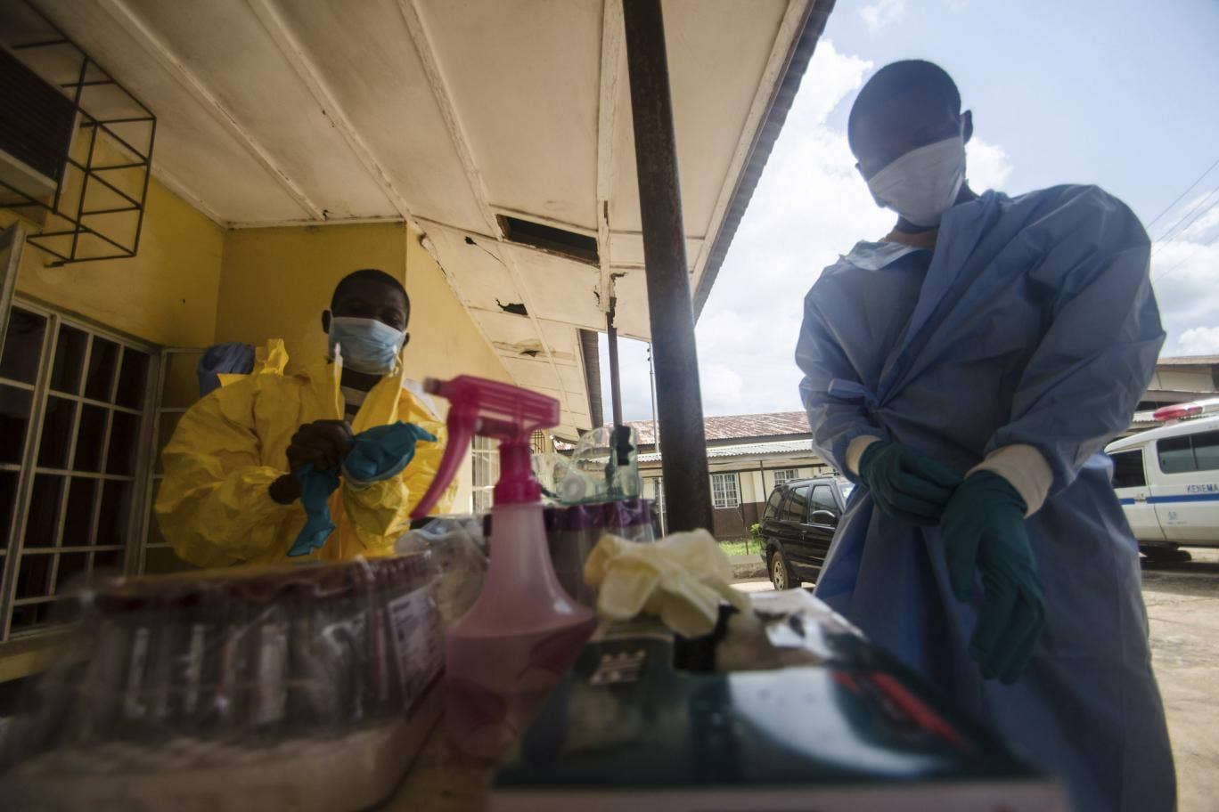 Health workers put on protective gear while working with suspected Ebola patients in Kenema, Sierra Leone