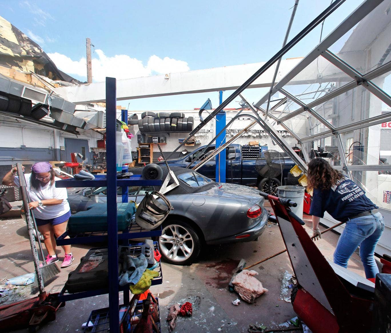 Master Auto manager Marie Annaloro, left, and Victoria Ohlson,right, sweep glass and debris in the service garage where the roof blew off in Revere, Mass