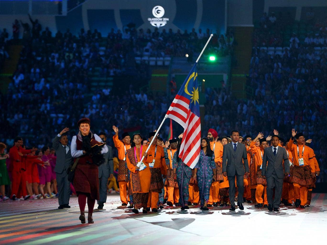 Flag bearer and Cyclist Fatehah Mustapa of Malaysia flies the flag at half mast during the Opening Ceremony for the Glasgow 2014 Commonwealth Games
