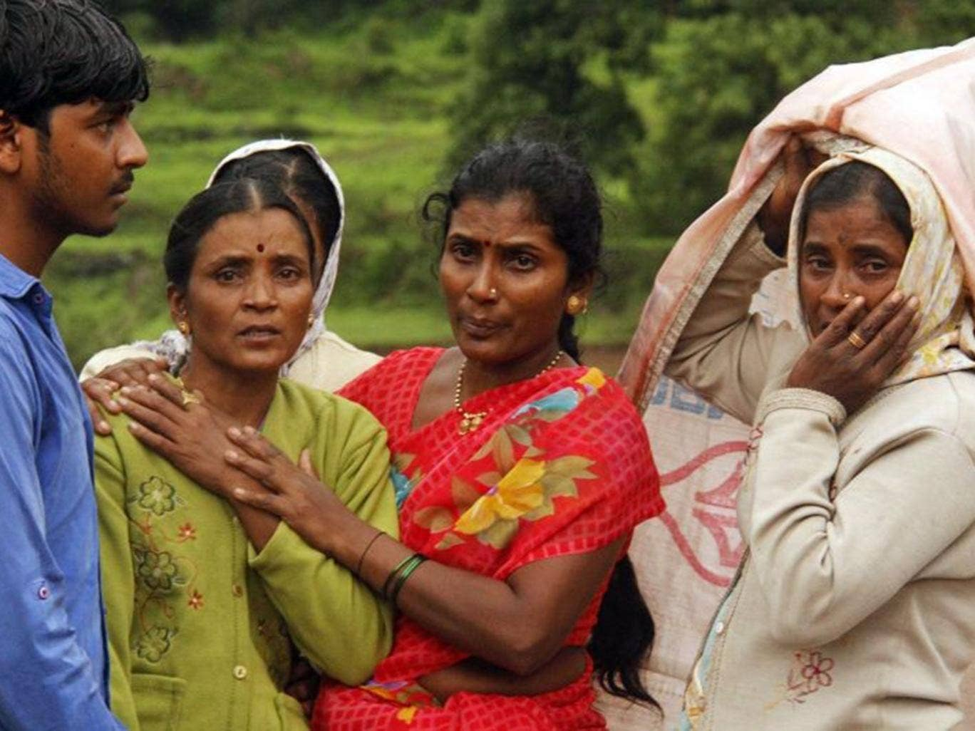 Villagers console each other as they watch a rescue operation at the site of a landslide in Malin village, in the western Indian state of Maharashtra, Wednesday, July 30, 2014.