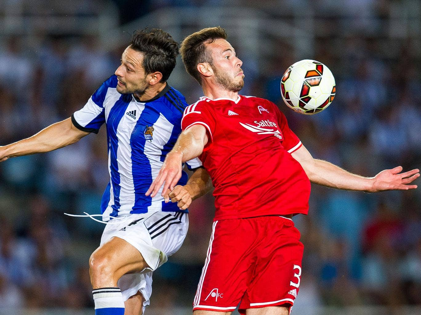 Andrew Considine of Aberdeen CF duels for the ball with Alberto de la Bella of Real Sociedad