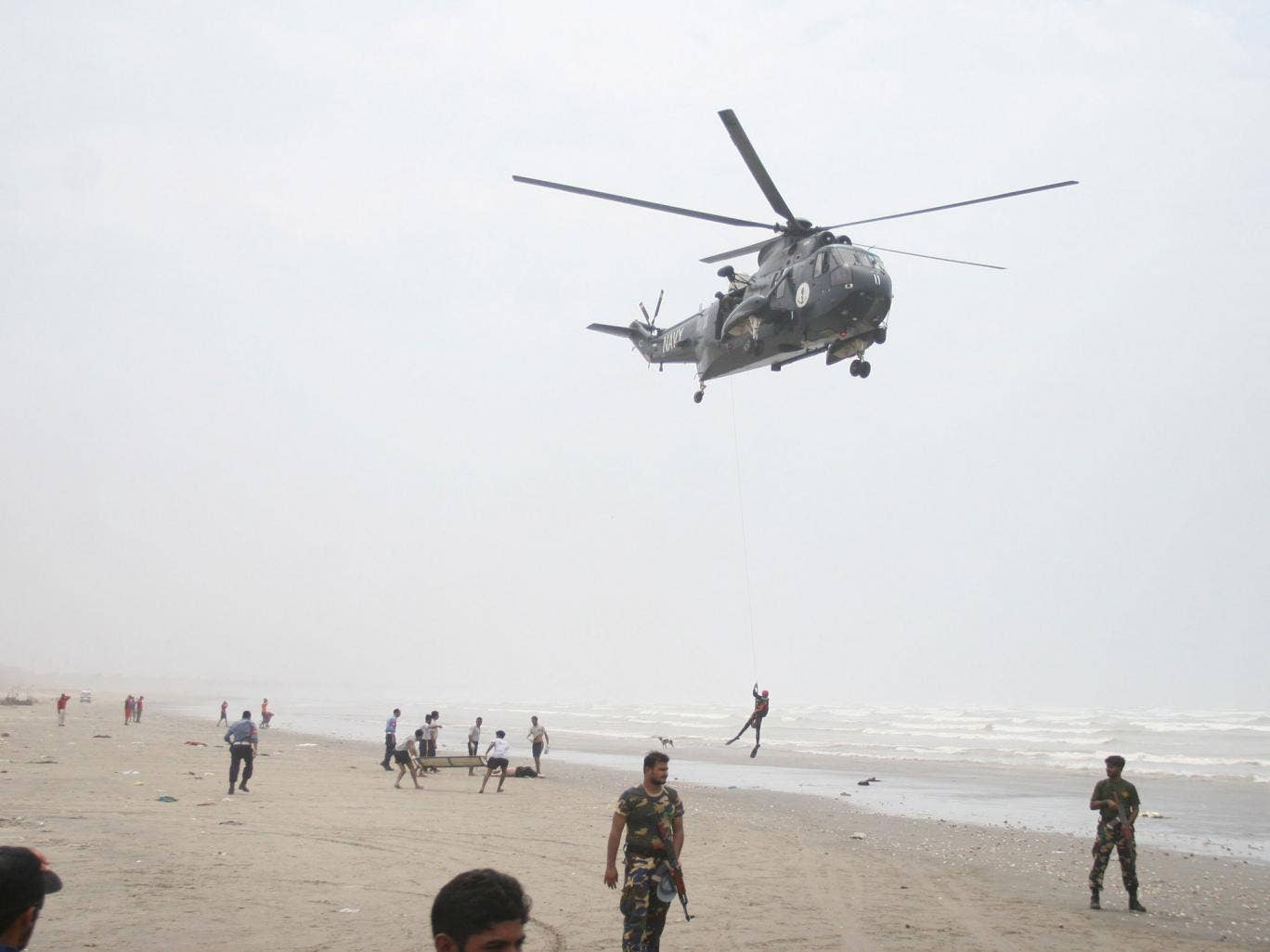 A Pakistani Navy Sea King helicopter flies a search and recovery mission for missing swimmers
