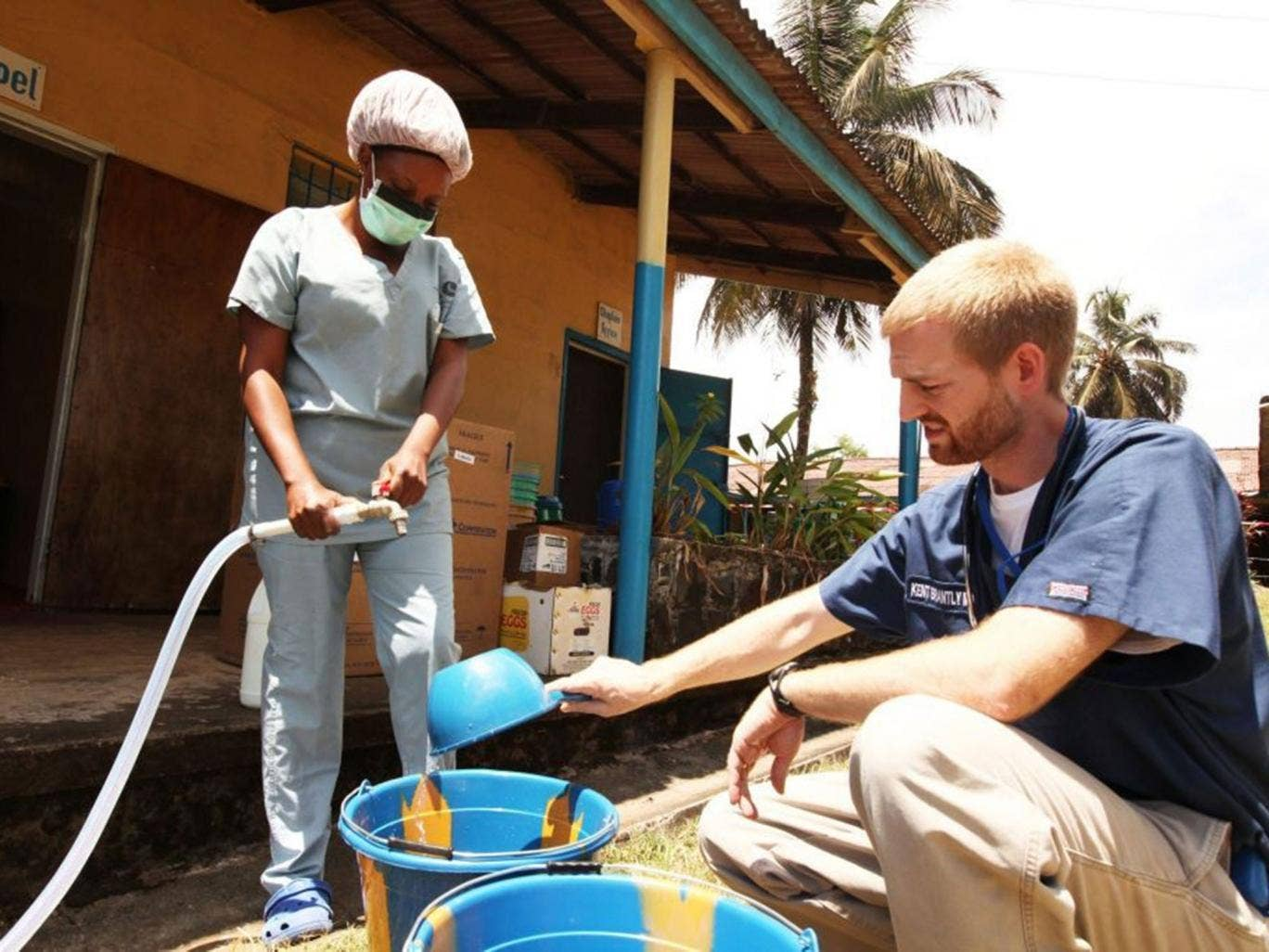 An aid worker helps with the measuring out the disinfectant
