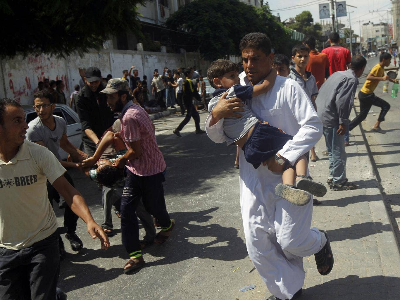 Palestinians carry injured people, including children, following a reported Israeli military strike on a UN school in Rafah