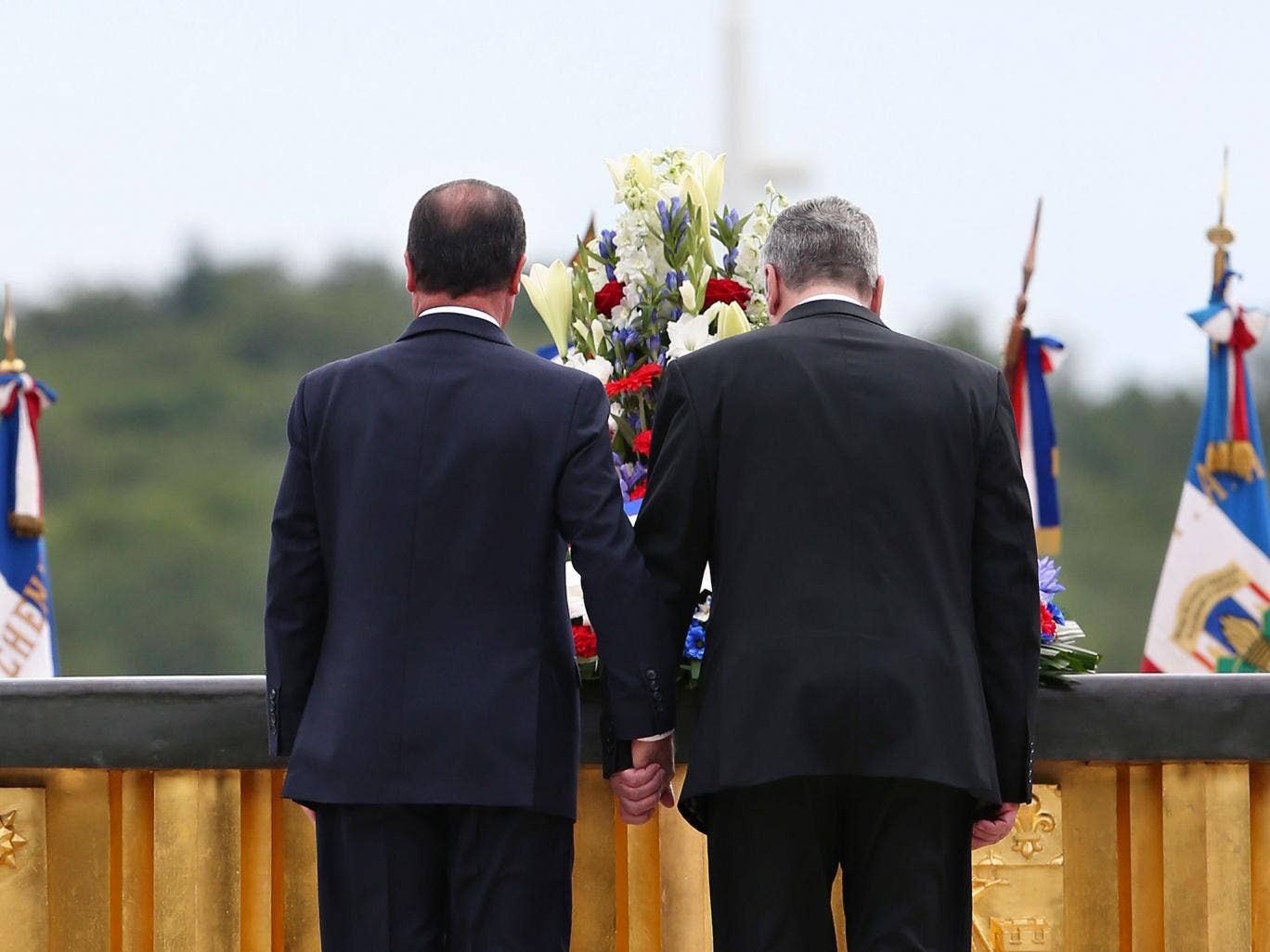 France's President François Hollande, left, and German President Joachim Gauck pay their respects at the National Monument in Wattwiller, eastern France