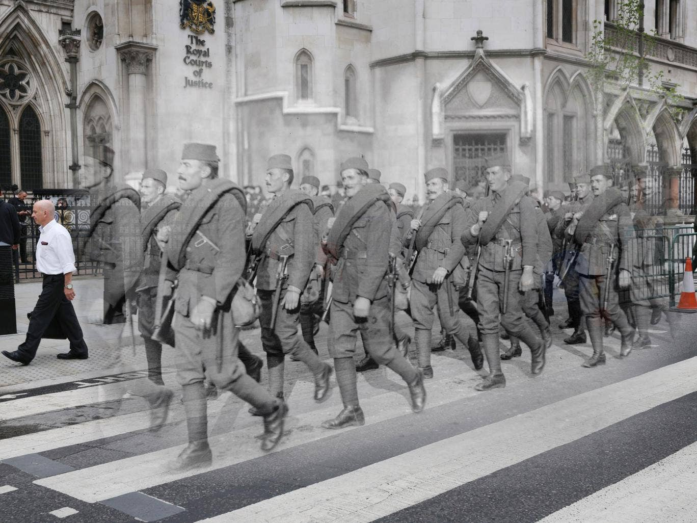 People pass the Royal Courts of Justice next to Serbian soldiers marching in the Lord Mayor's show, London, in the last days of the First World War in November 1918