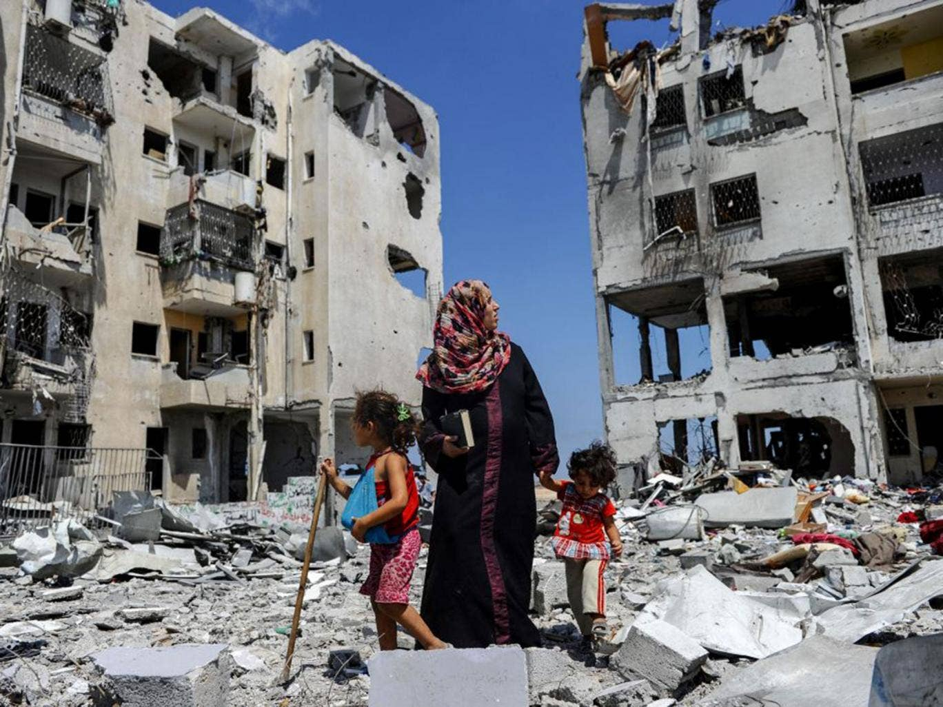 Palestinians sift through the rubble in Beit Lahia, Gaza, in a search for useful belongings