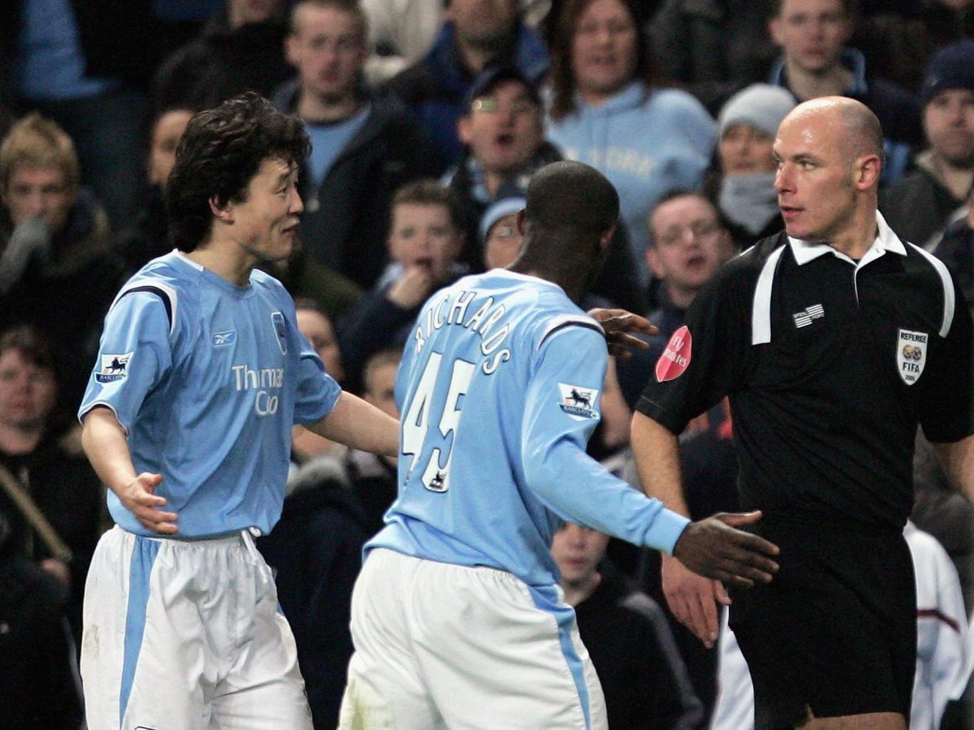 Howard Webb (right) sends off Manchester City defender Sun Jihai (left)