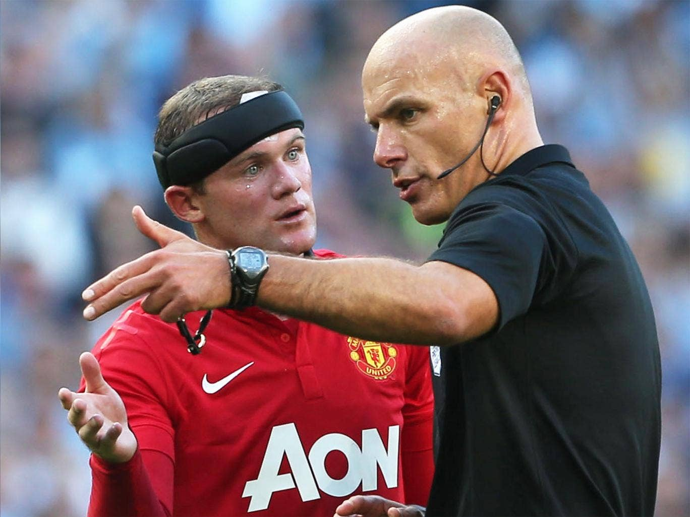Howard Webb (right) explains a decision to Manchester United's Wayne Rooney