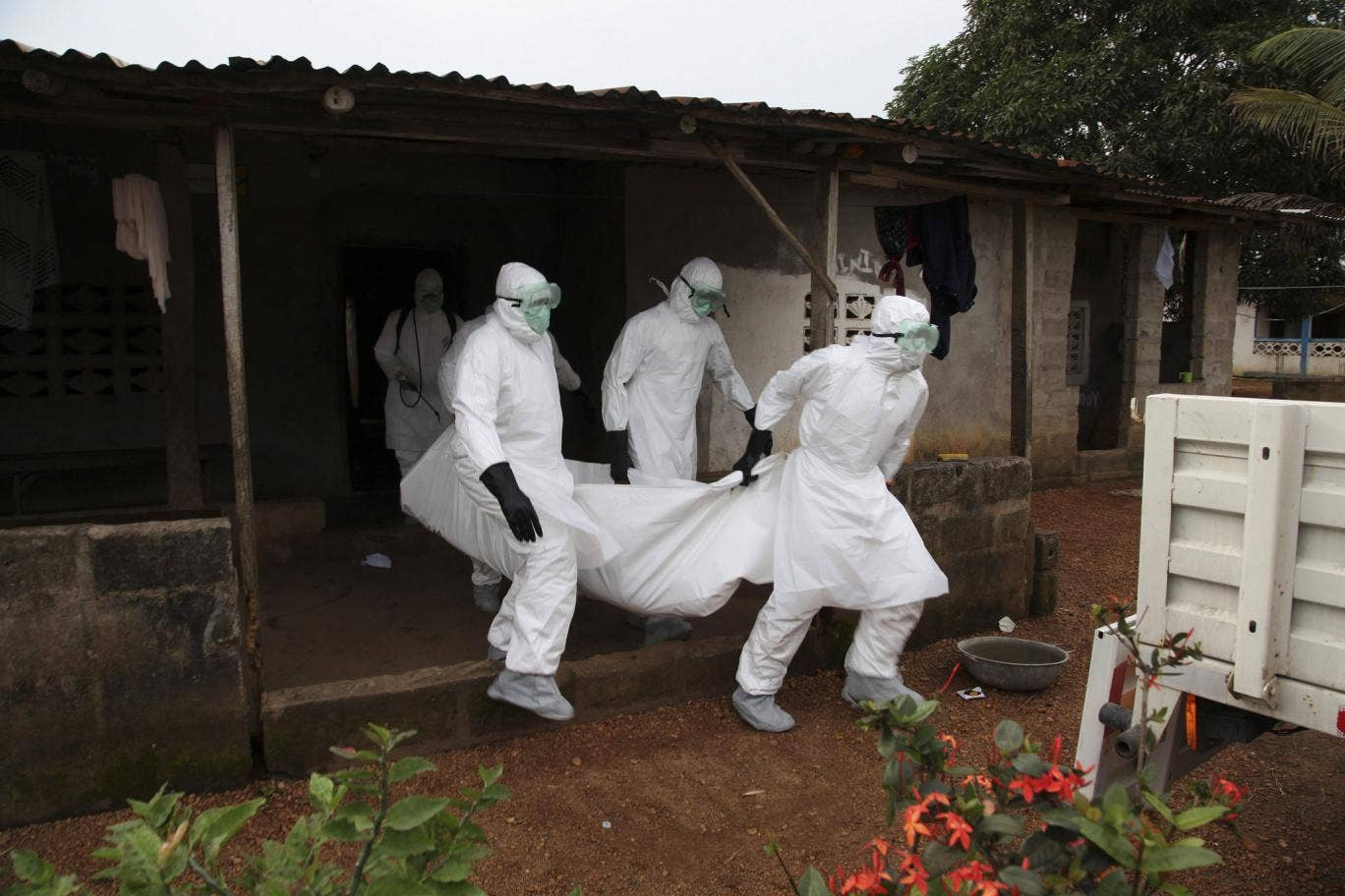 Liberian nurses carry the body of an Ebola victim from a house for burial in the Banjor Community on the outskirts of Monrovia, Liberia 6 August 2014.