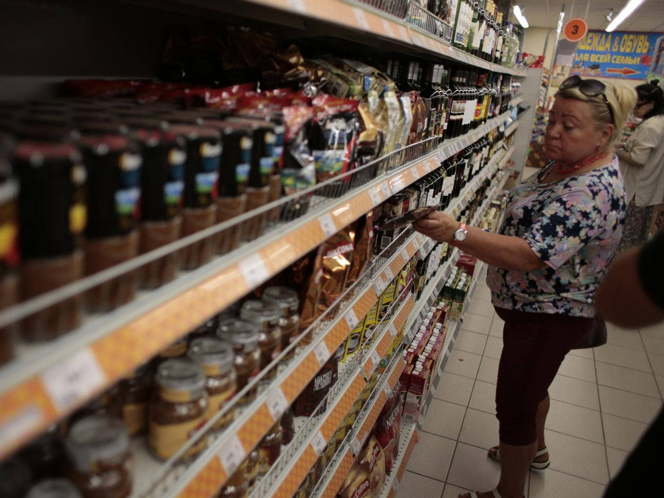 A woman choses sweets at a counter with imported food stuffs at a supermarket in downtown Moscow on Thursday, Aug. 7, 2014