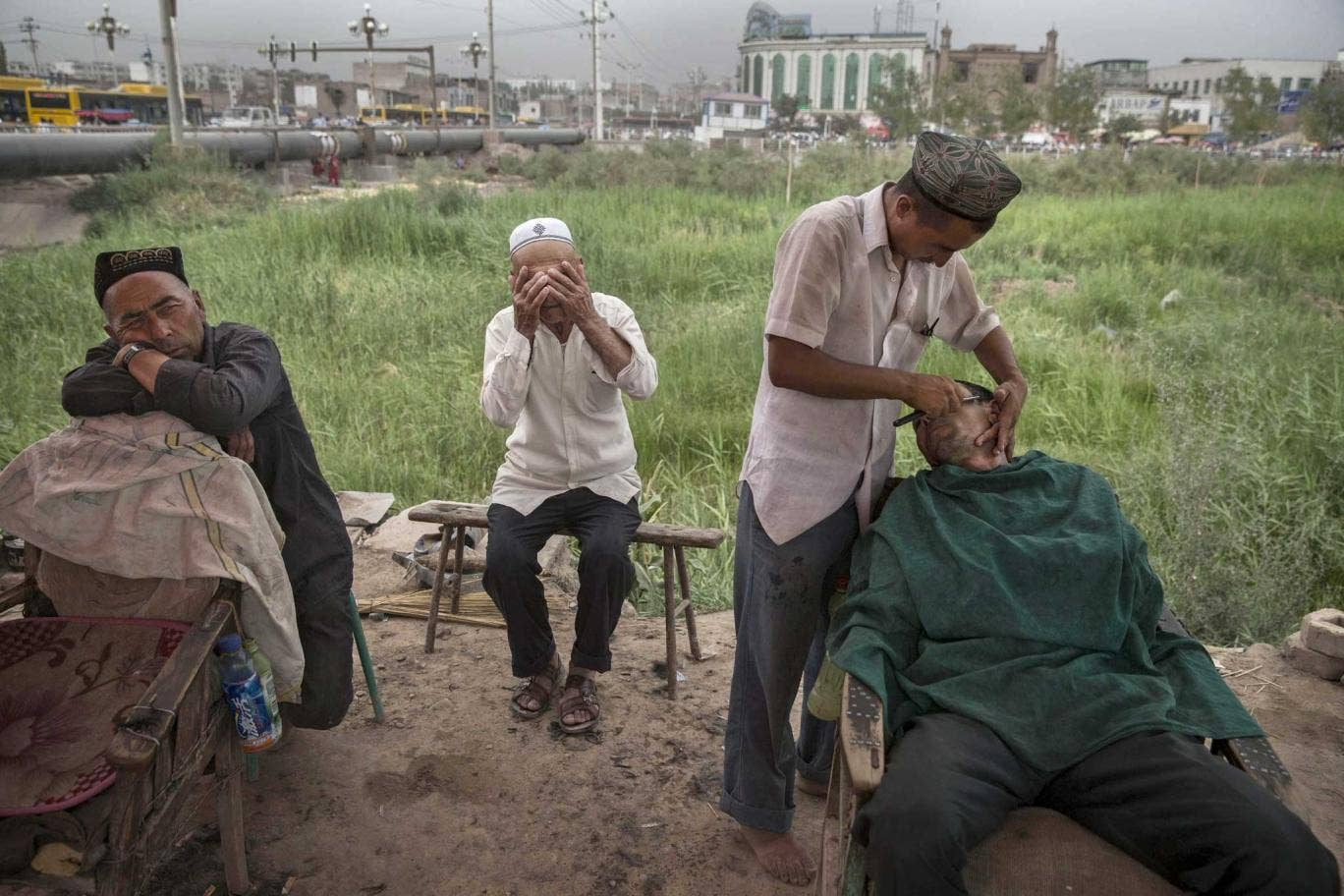 Scraping a living: an Uighur shaves customers at his open air stall in Xinjiang province, the site of recent ethnic unrest