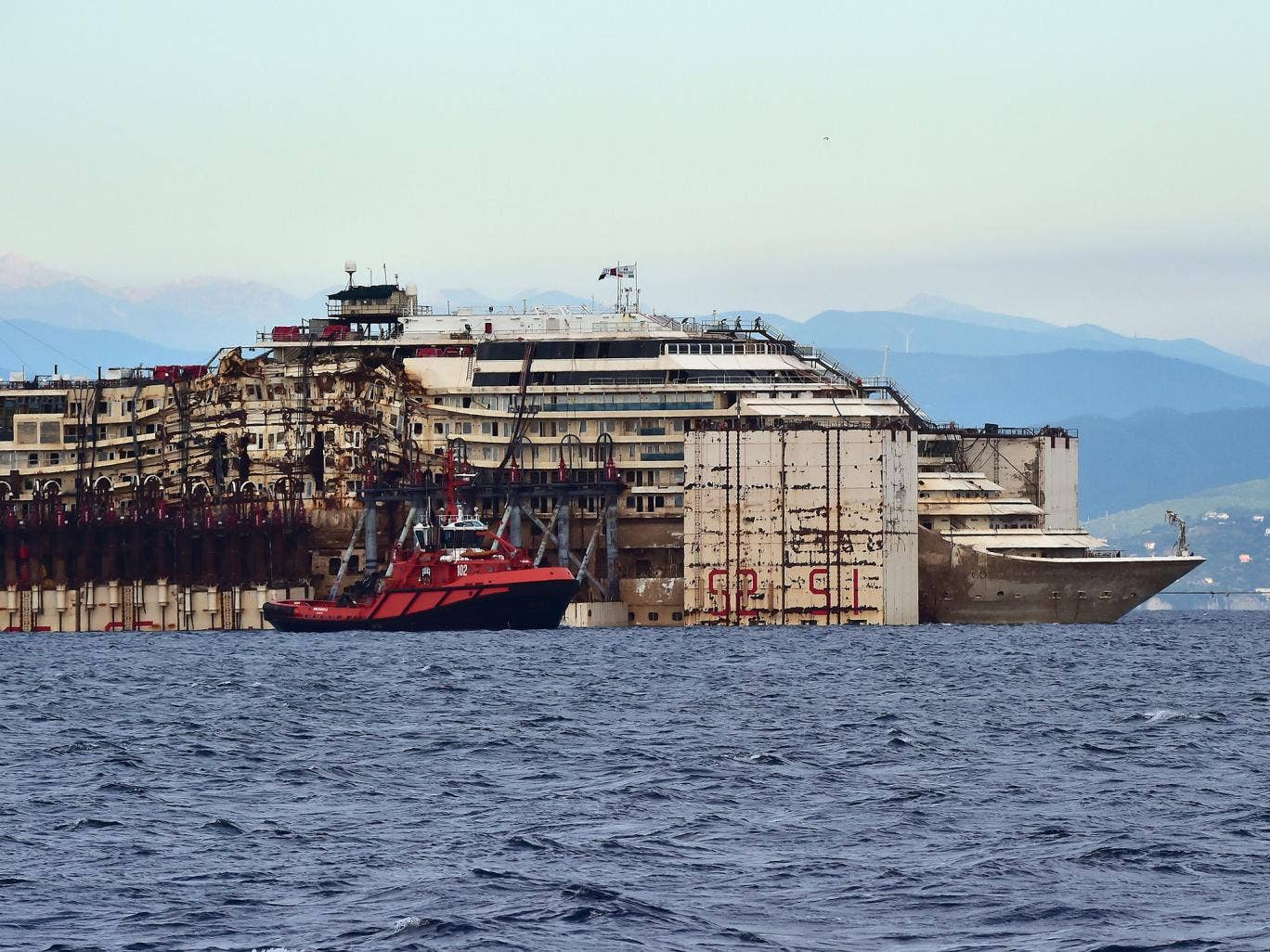 The refloated wreck of the Costa Concordia cruise ship is being dragged to the harbor of Pra di Voltri near Genoa