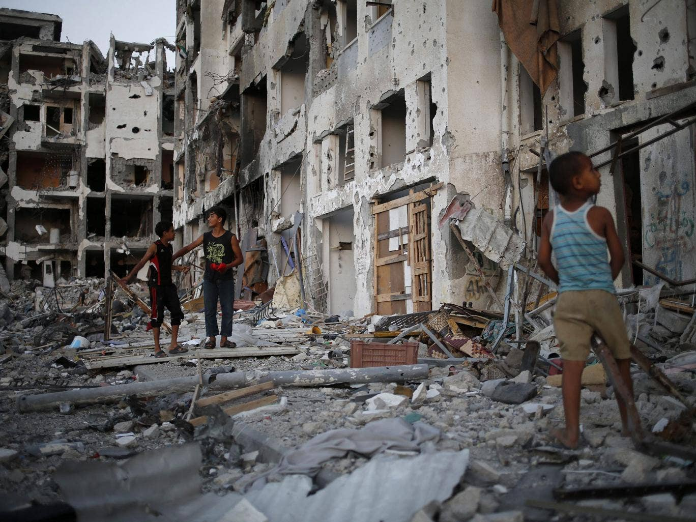 Palestinian boys play among the rubbles of a destroyed AL-Nada towers, hours before a 72-hours ceasefire between Israel and Hamas will come to an end in Beit Lahiya town in the northern Gaza, 07 August 2014