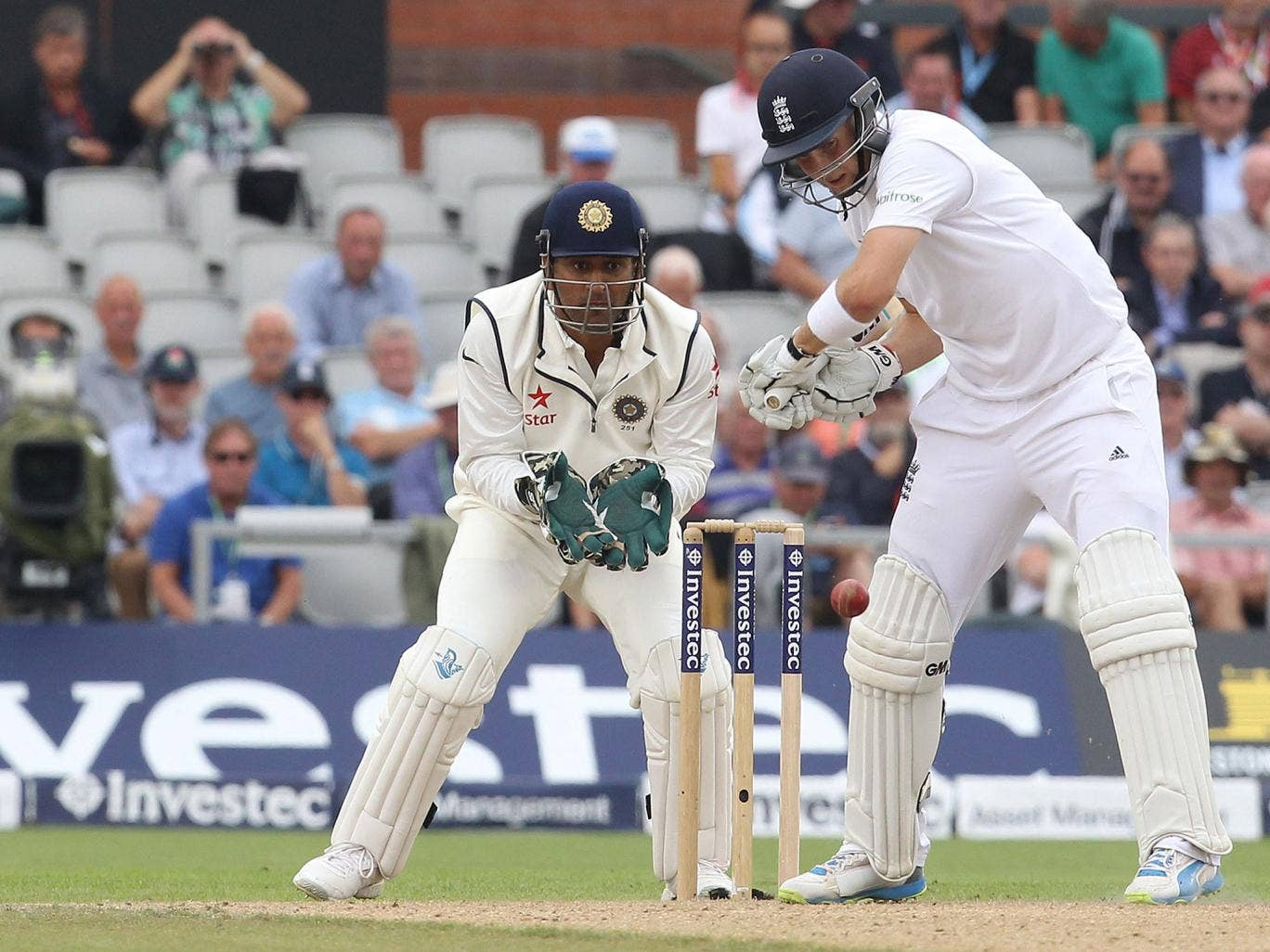 MS Dhoni looks on as Joe Root plays a shot during the fourth Test