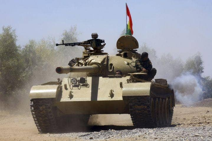 Kurdish peshmerga troops patrol in a tank during an operation against Islamic State militants in Makhmur, on the outskirts of the province of Nineveh August 7, 2014.