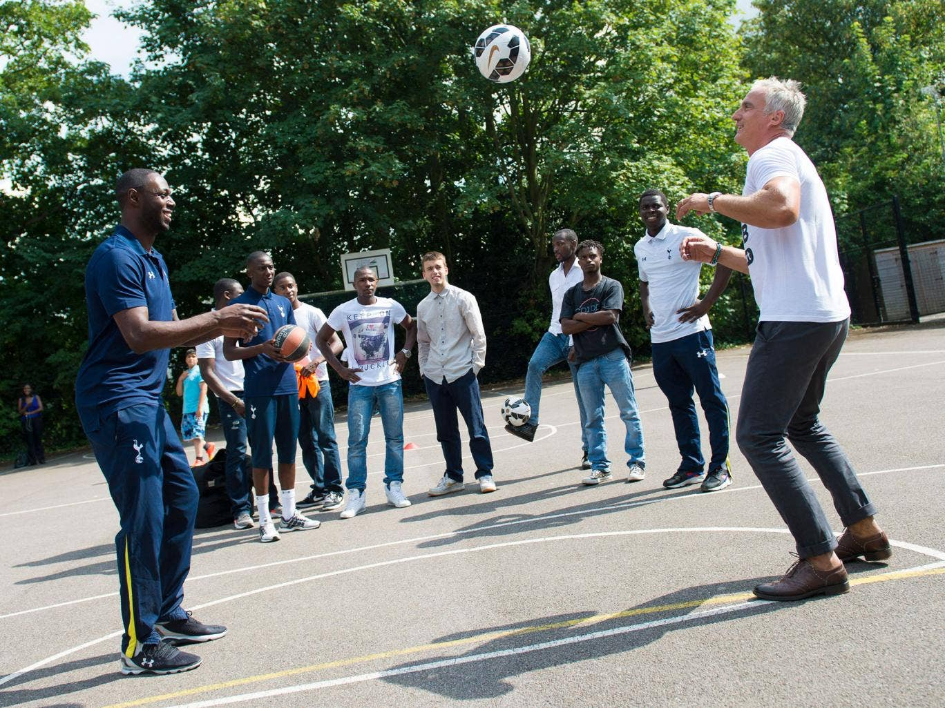 Ledley King and David Ginola perform keepy-uppys in front of members of the To Care Is To Do program
