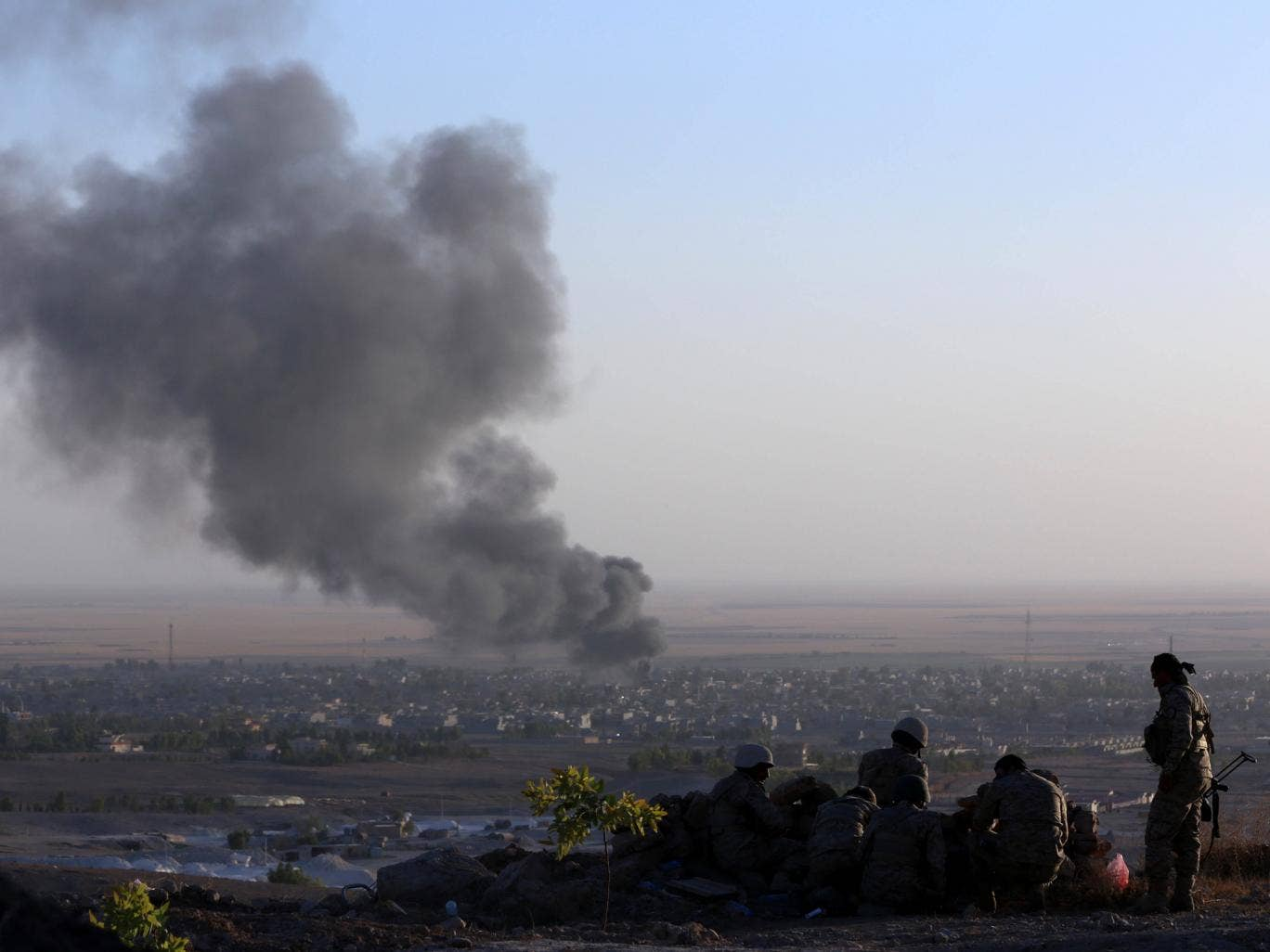 Iraqi Kurdish Peshmerga fighters look on as smoke billows from the town Makhmur, about 175 miles north of the capital Baghdad, during clashes with Isis militants