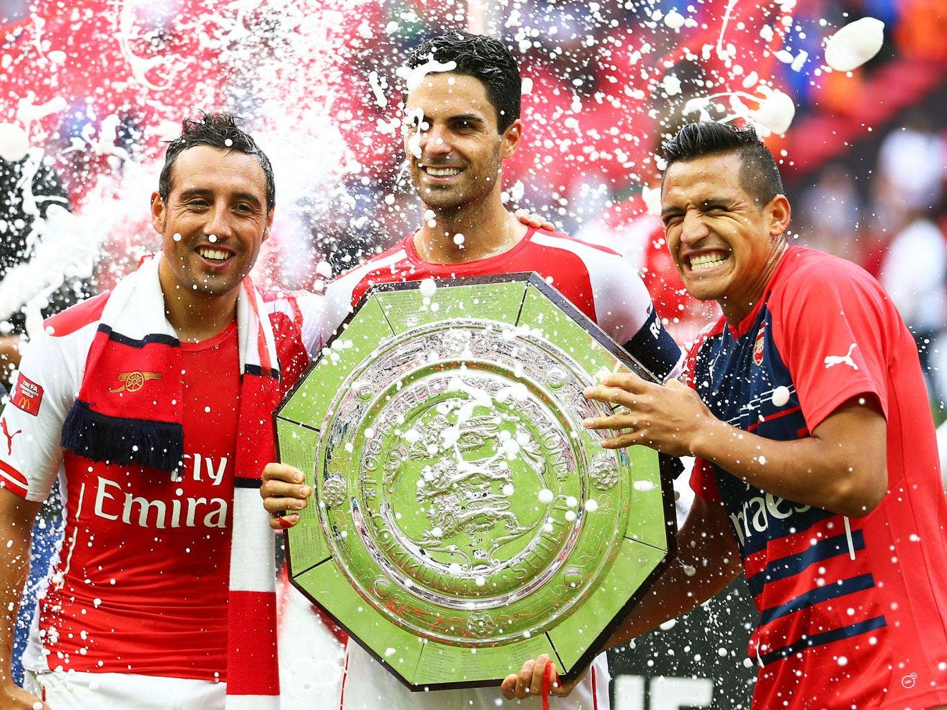 Mikel Arteta poses with the Community Shield alongside Santi Cazorla (left) and Alexis Sanchez (right)