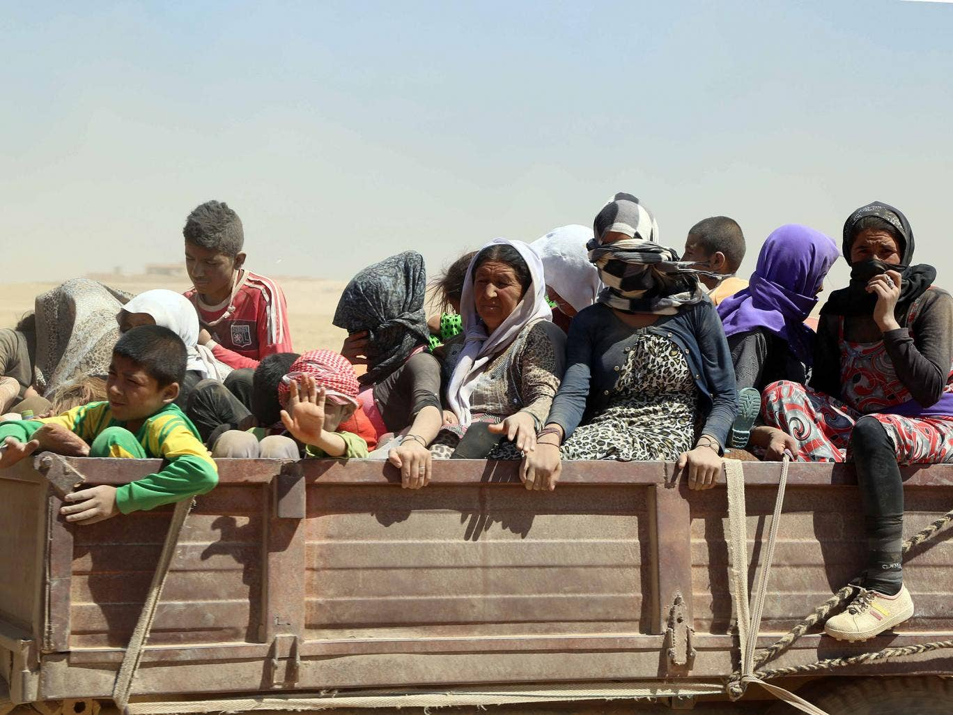 Yazidis who had fled to the Sinjar mountains to escape Isis fighters are brought to safety in Mosul by Kurdish Peshmerga forces