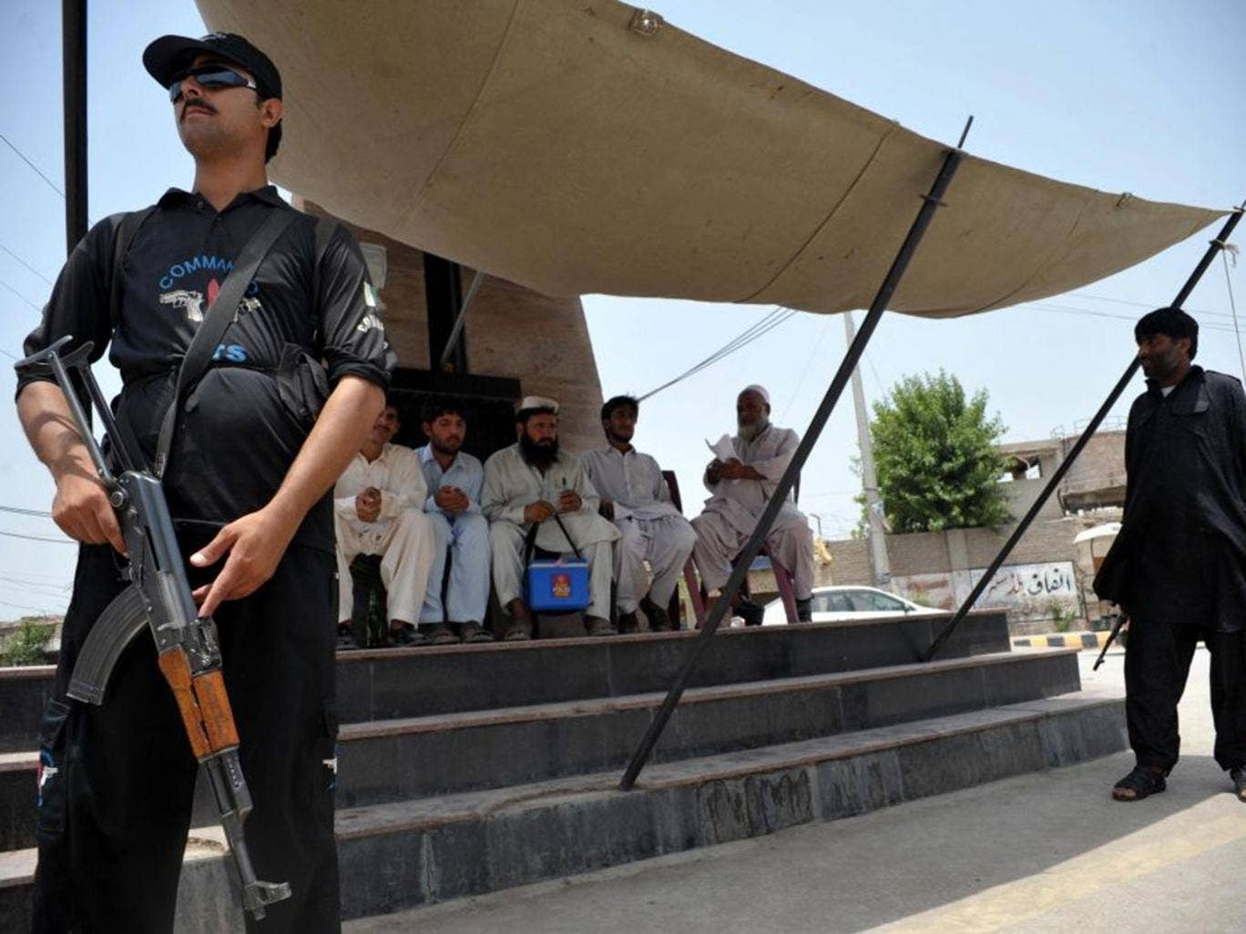 Pakistani police commandos guard a polio vaccination team at a security checkpoint in Bannu