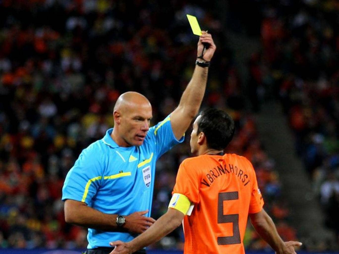 Howard Webb shows a yellow card to Giovanni van Bronckhorst at Soccer City while refereeing the 2010 World Cup final between the Netherlands and Spain