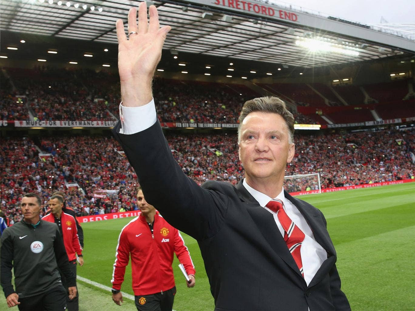 Louis van Gaal signs salutes United fans before the match
