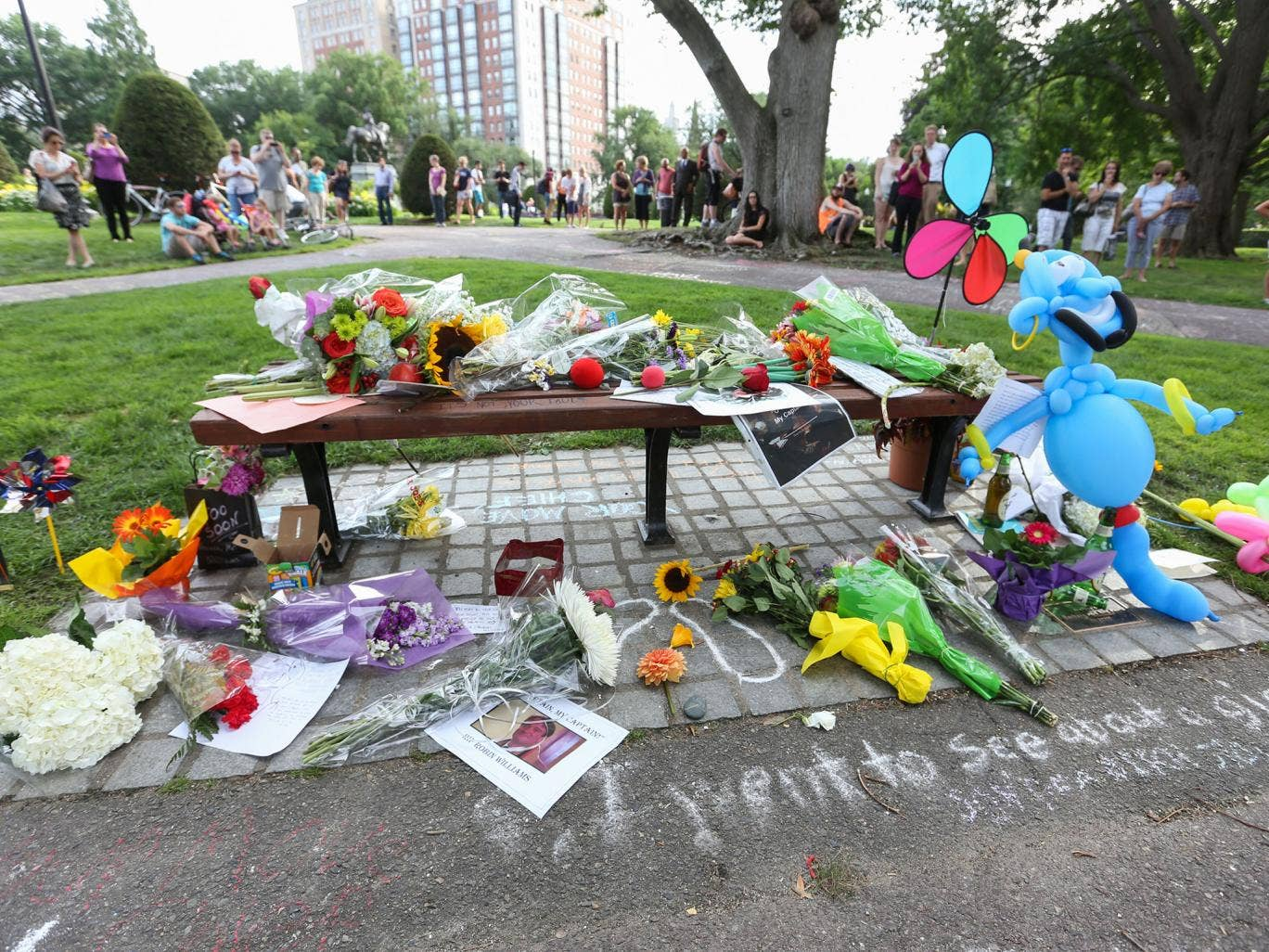 Crowds gather to pay tribute to fallen actor Robin Williams near the bench in the Boston Public Garden in Boston, Massachusetts where Robin Williams filmed a famous scene with actor Matt Damon for the movie 'Good Will Hunting'